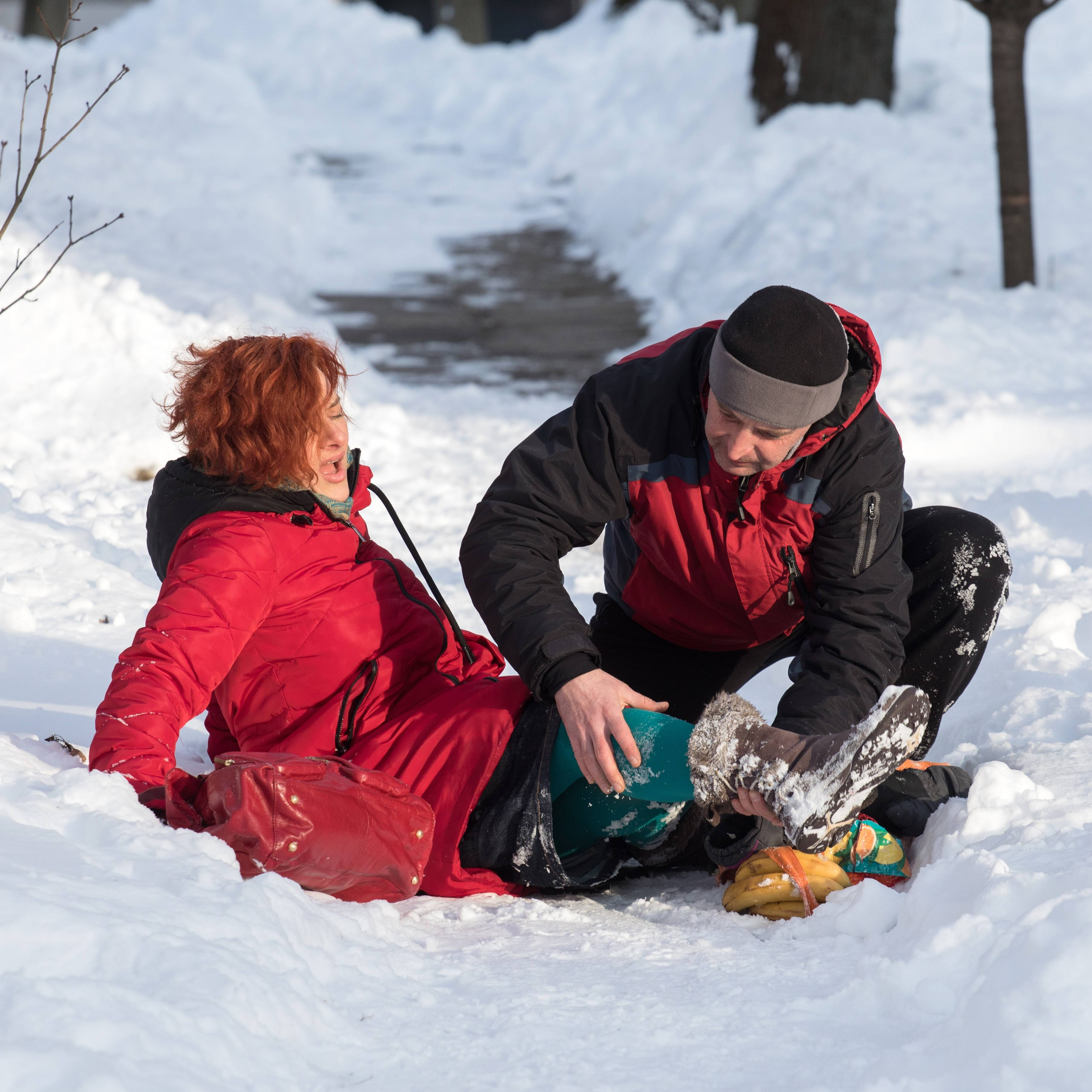 a woman who has fallen on a snowy, icy path in the winter woods and a male friend is helping her
