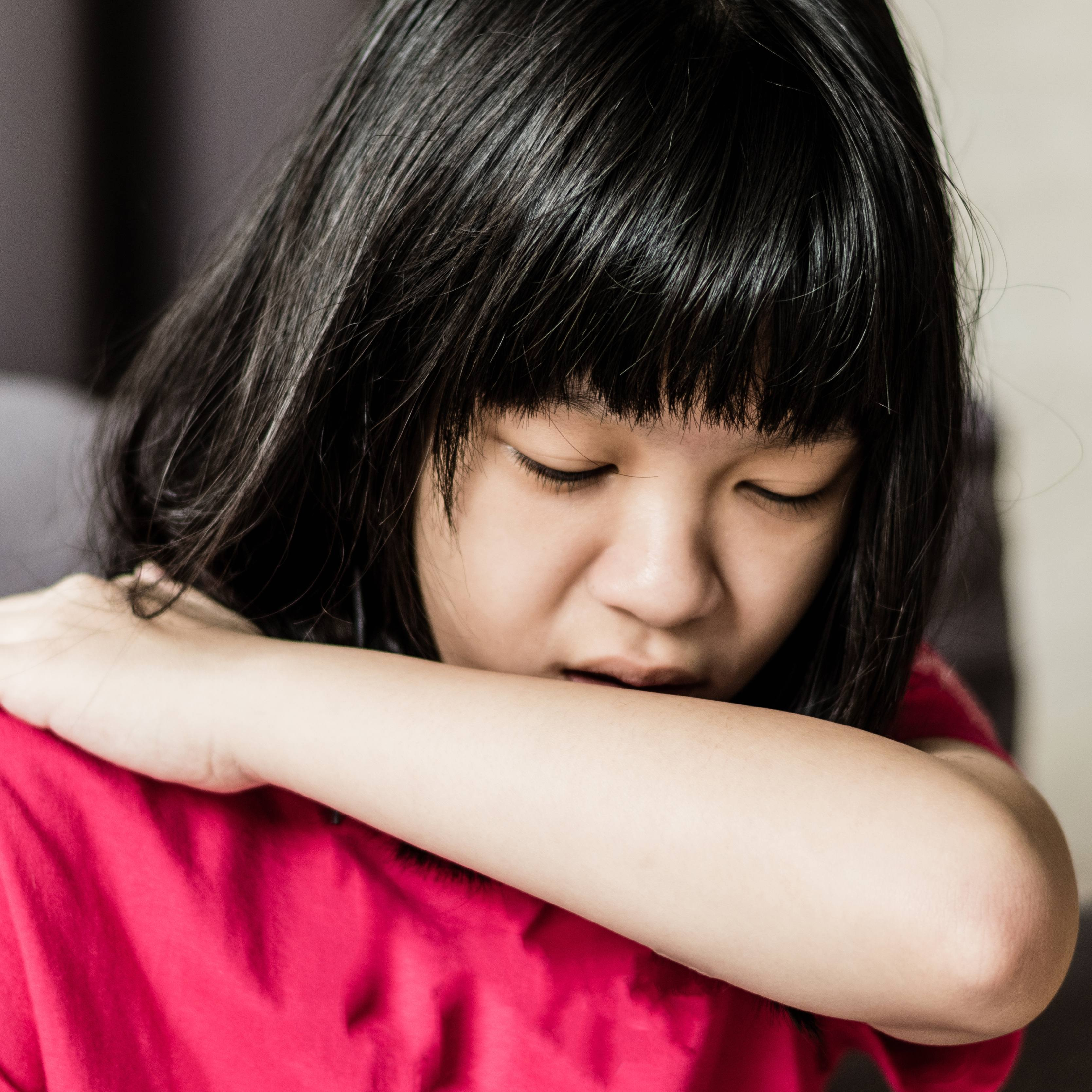 a young Asian girl who might be sick with a cold or the flu, is coughing into her elbow