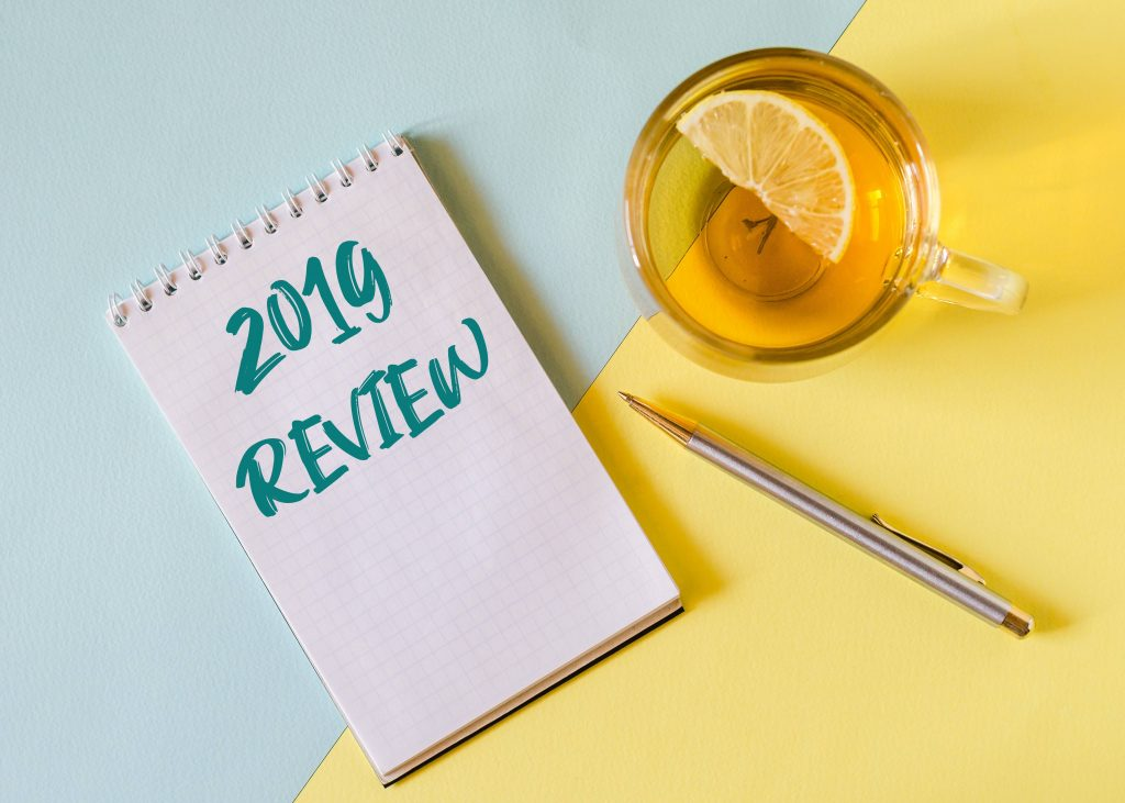a mug of tea with lemon, a pen, and a notebook with the words 2019 REVIEW
