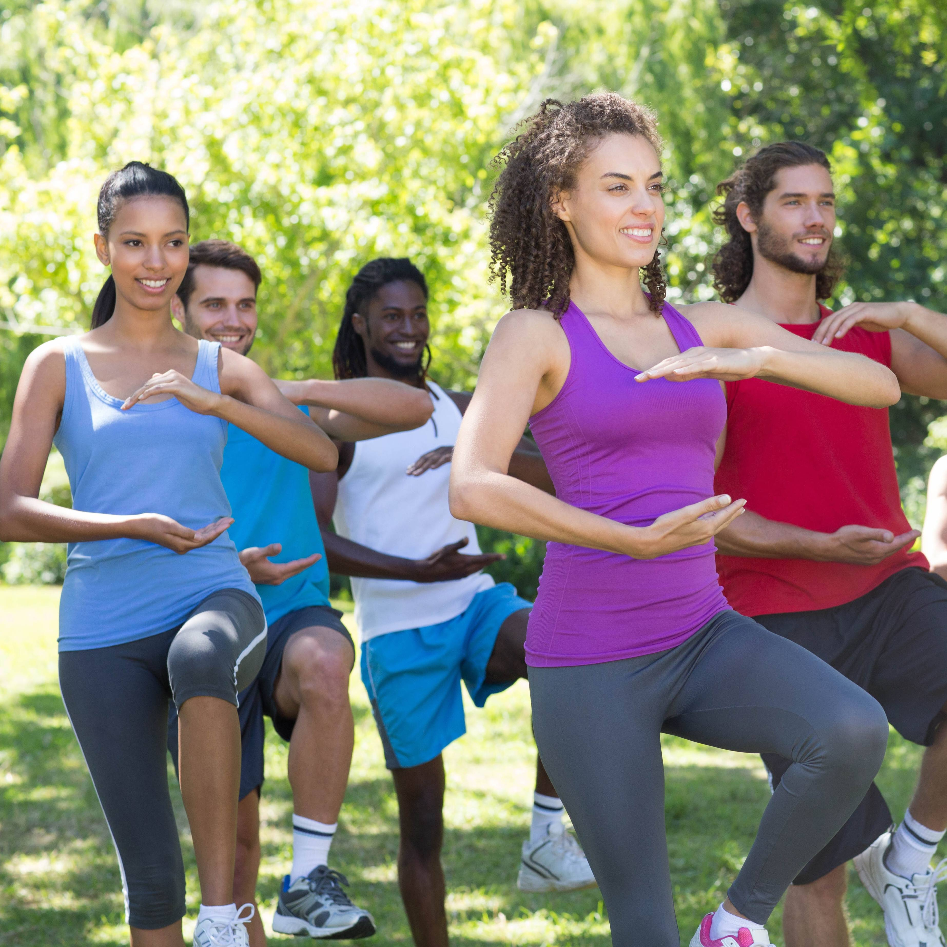 a group of people, athletes outside in a park stretching and exercising, perhaps doing yoga or Tai chi