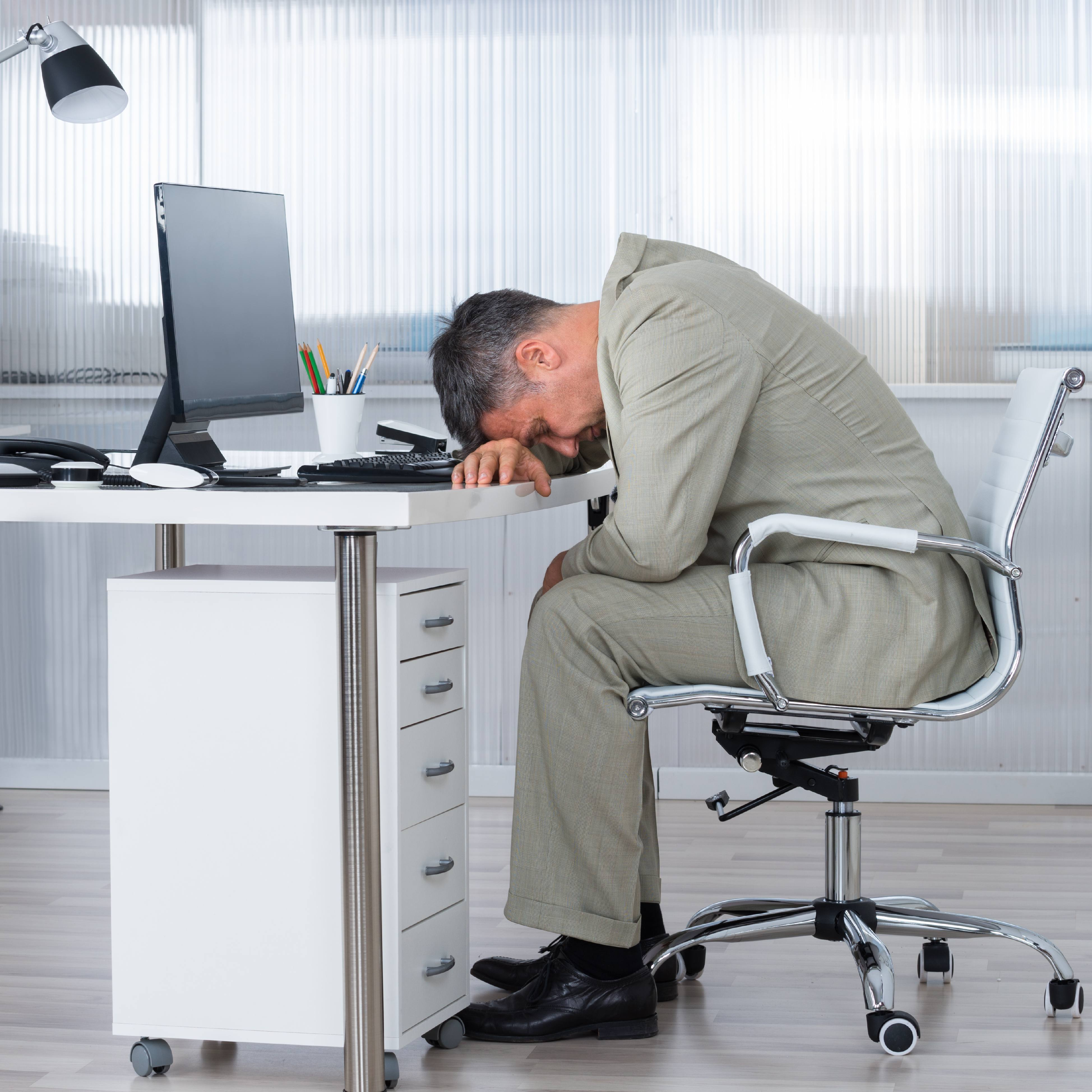 a Caucasian businessman wearing a suit, sitting in a chair, slumped over his desk that has a computer monitor and he looks exhausted, tired and stressed or perhaps asleep