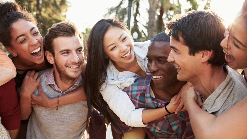 a diverse group of young people hugging and laughing, having fun shutterstock_172218053