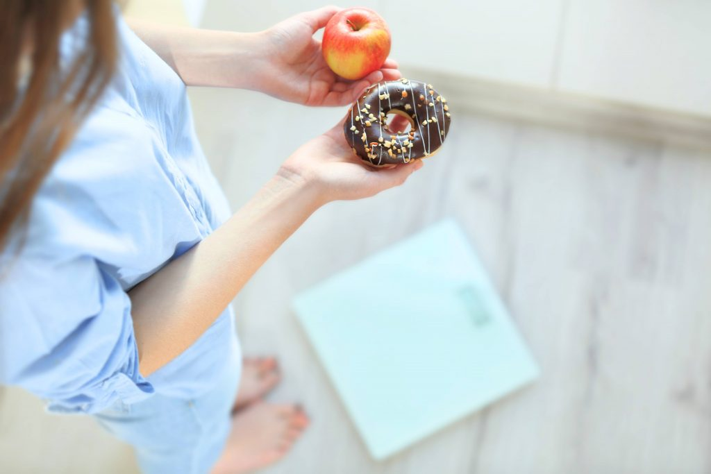 a woman holding an apple in one hand a sprinkled donut in the other, while standing near a scale to weigh herself
