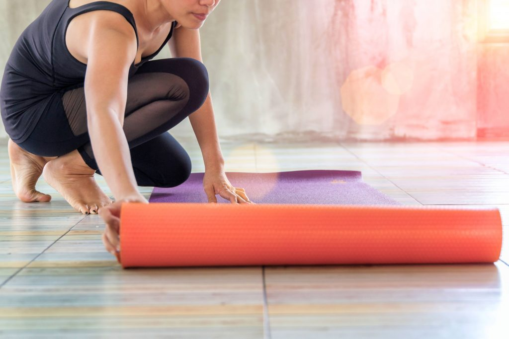 a woman in a yoga studio rolling out an exercise yoga mat on the floor with warm sunshine streaming in a window