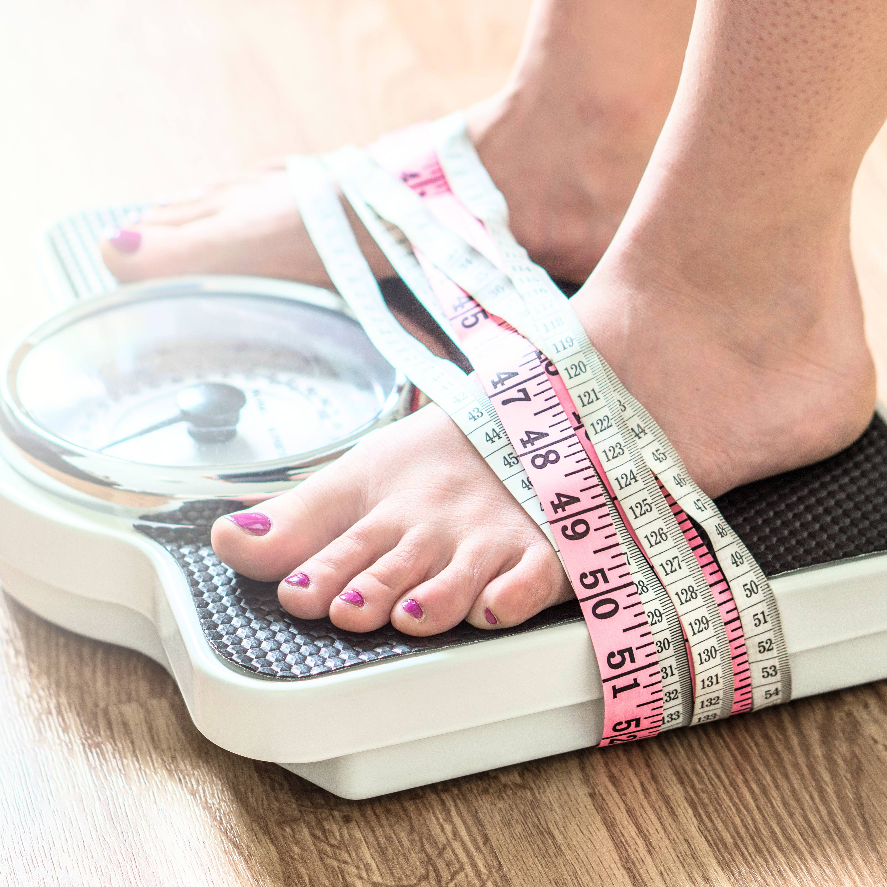 a woman standing on a scale to weigh herself and measuring tapes are wrapped around her feet and the scale