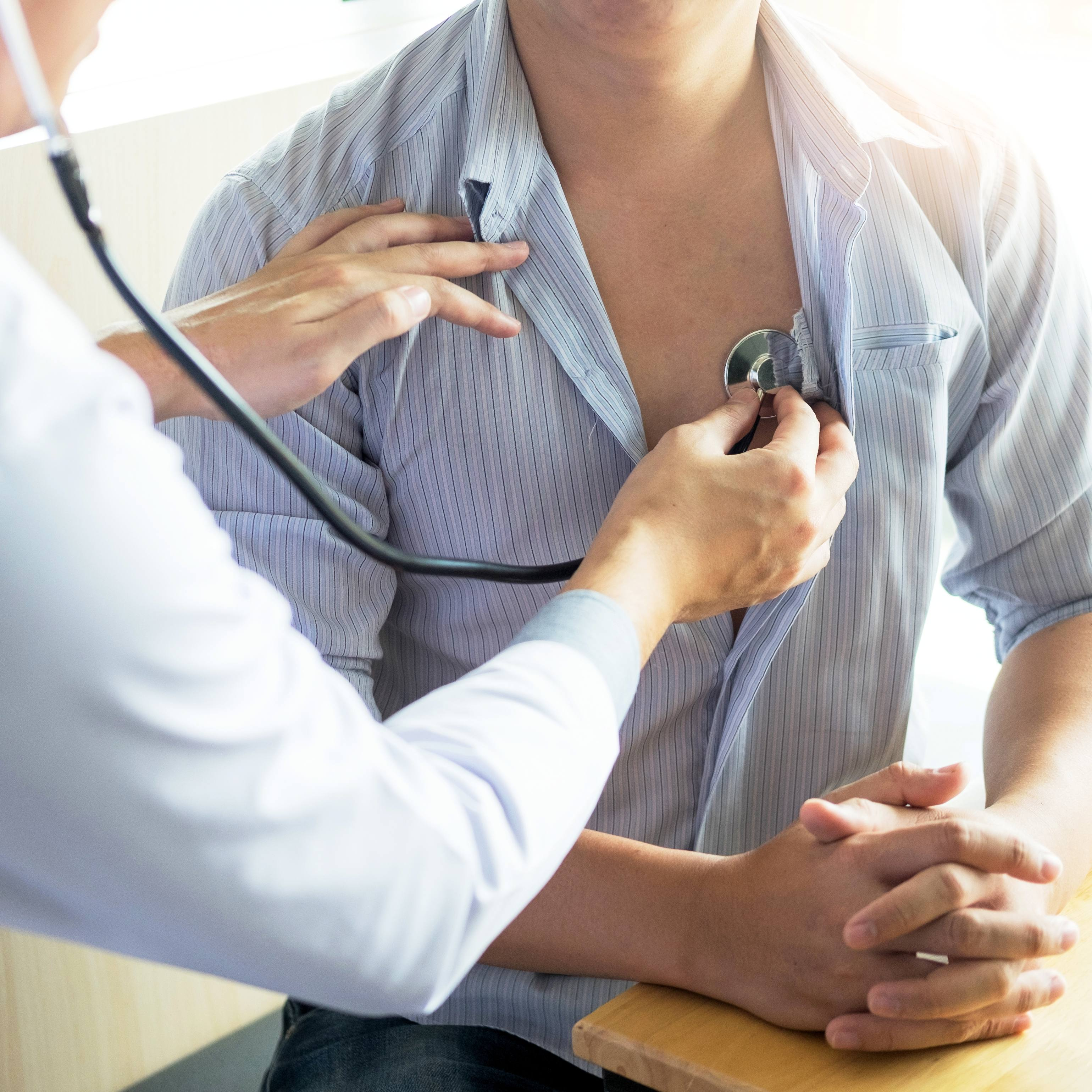 a young man in an exam room with his shirt open so a medical person, perhaps a doctor or nurse practitioner can listen to his heart with a stethoscope