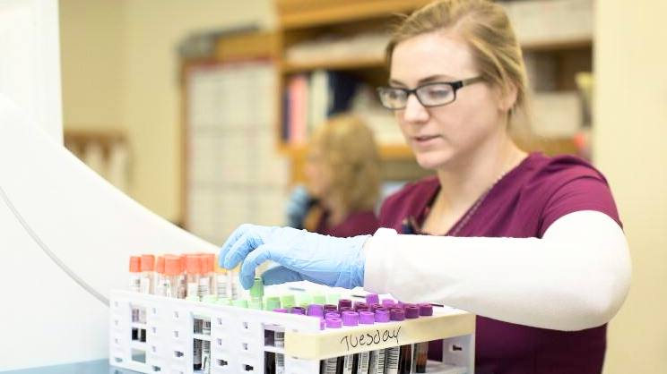 a young white woman wearing glasses and medical gloves working in a research lab with blood samples