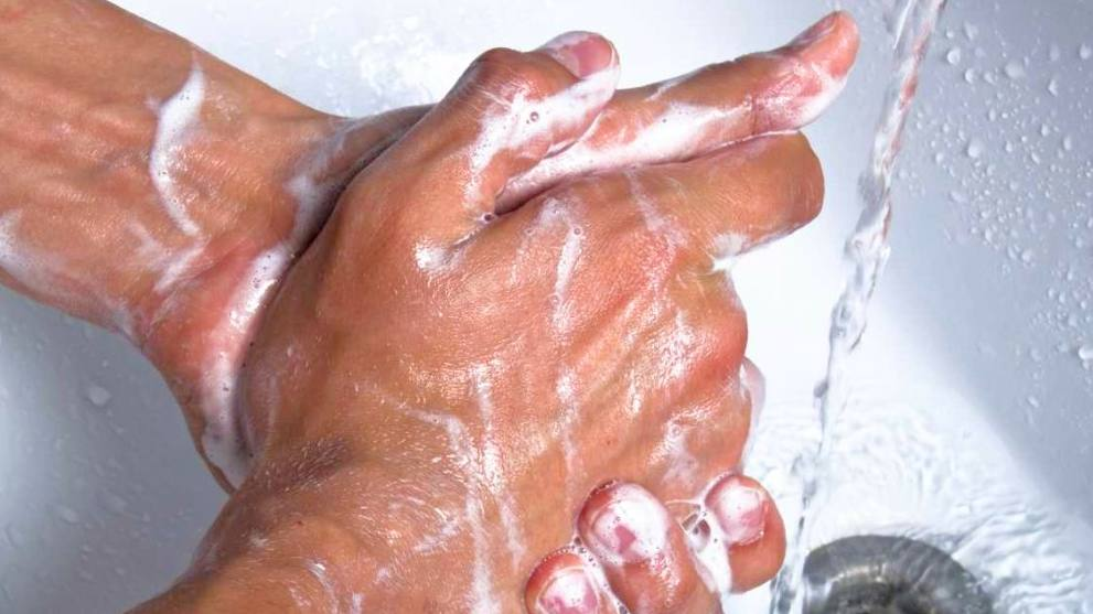 closeup of adult male hands washing with soap and running water in a sink