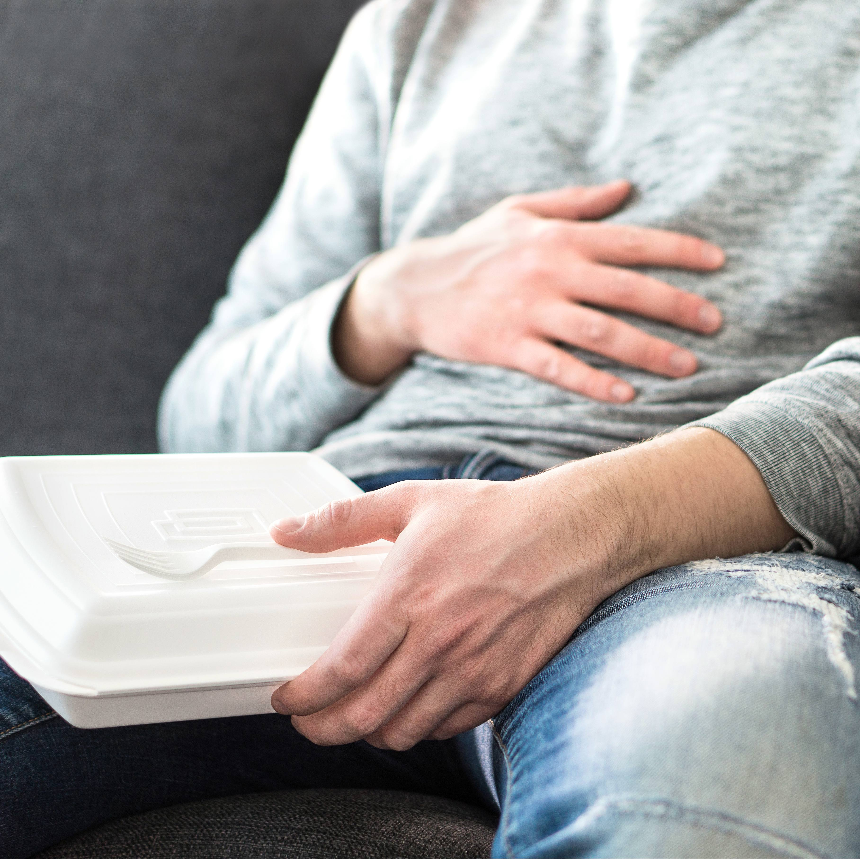 a white man in jeans, sitting on a couch and holding a take out food box, holding his stomach like he's sick or ill with a stomach ache, maybe gastroenterology and indigestion problems with gas