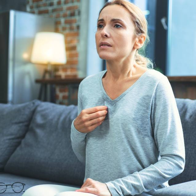 a white woman wearing a grey shirt, sitting on a couch and sweating, looking scared, worried, concerned and holding her hand to her chest like she's maybe panicking