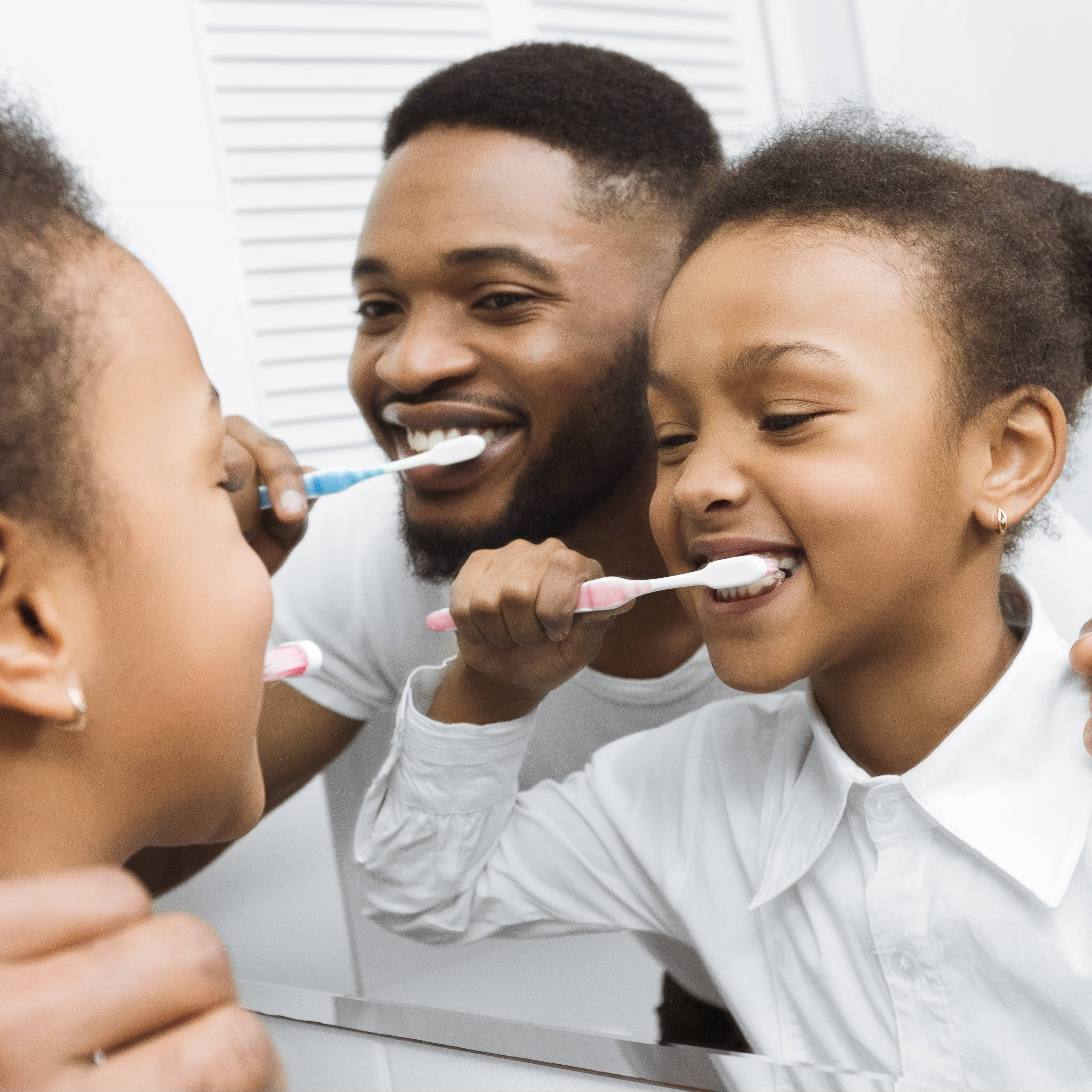 a little African American girl looking in the mirror and brushing her teeth, with perhaps her African American father looking over her shoulder and brushing his teeth, too
