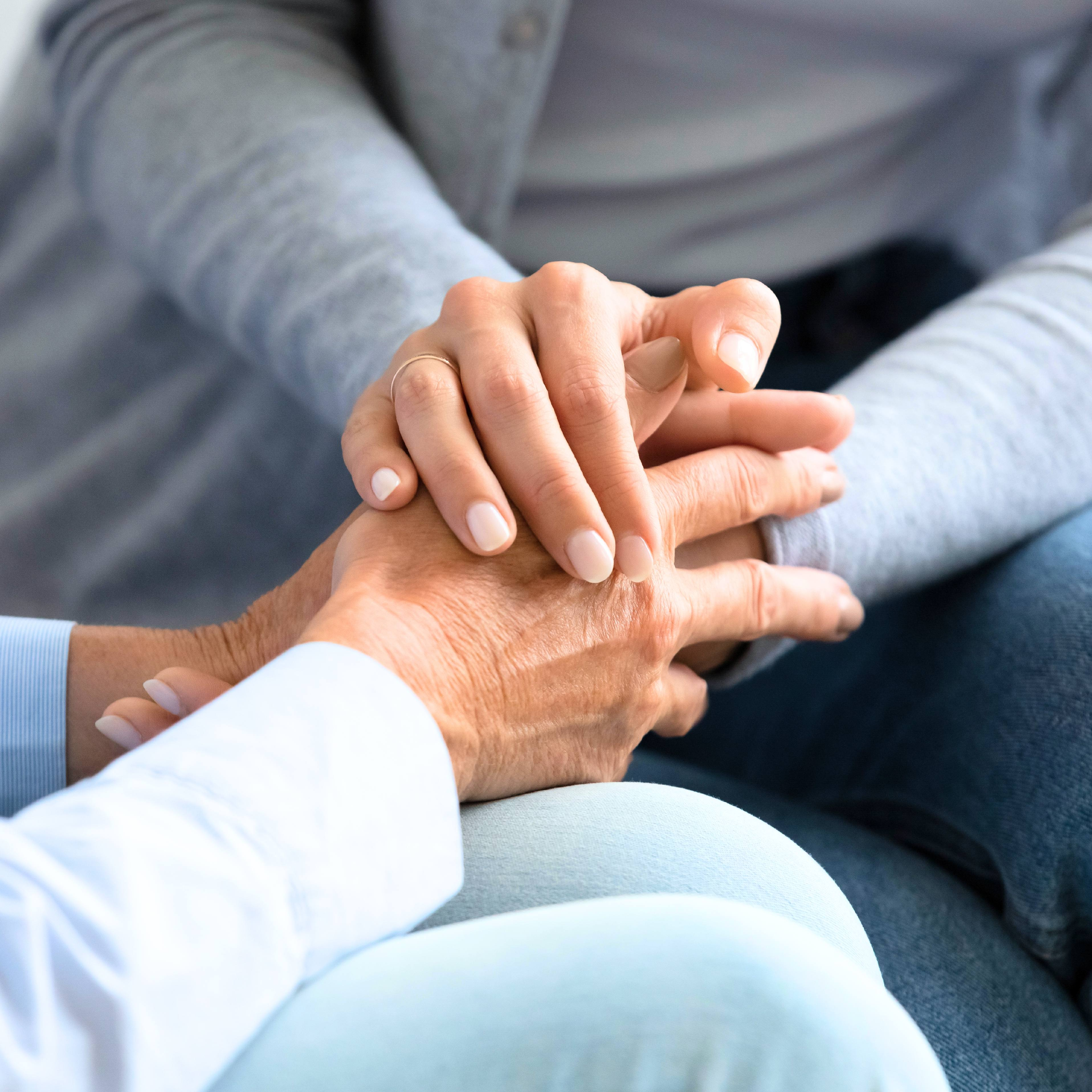 a young white woman sitting on a couch, holding the hands of an older white woman, offering compassion, sympathy and care