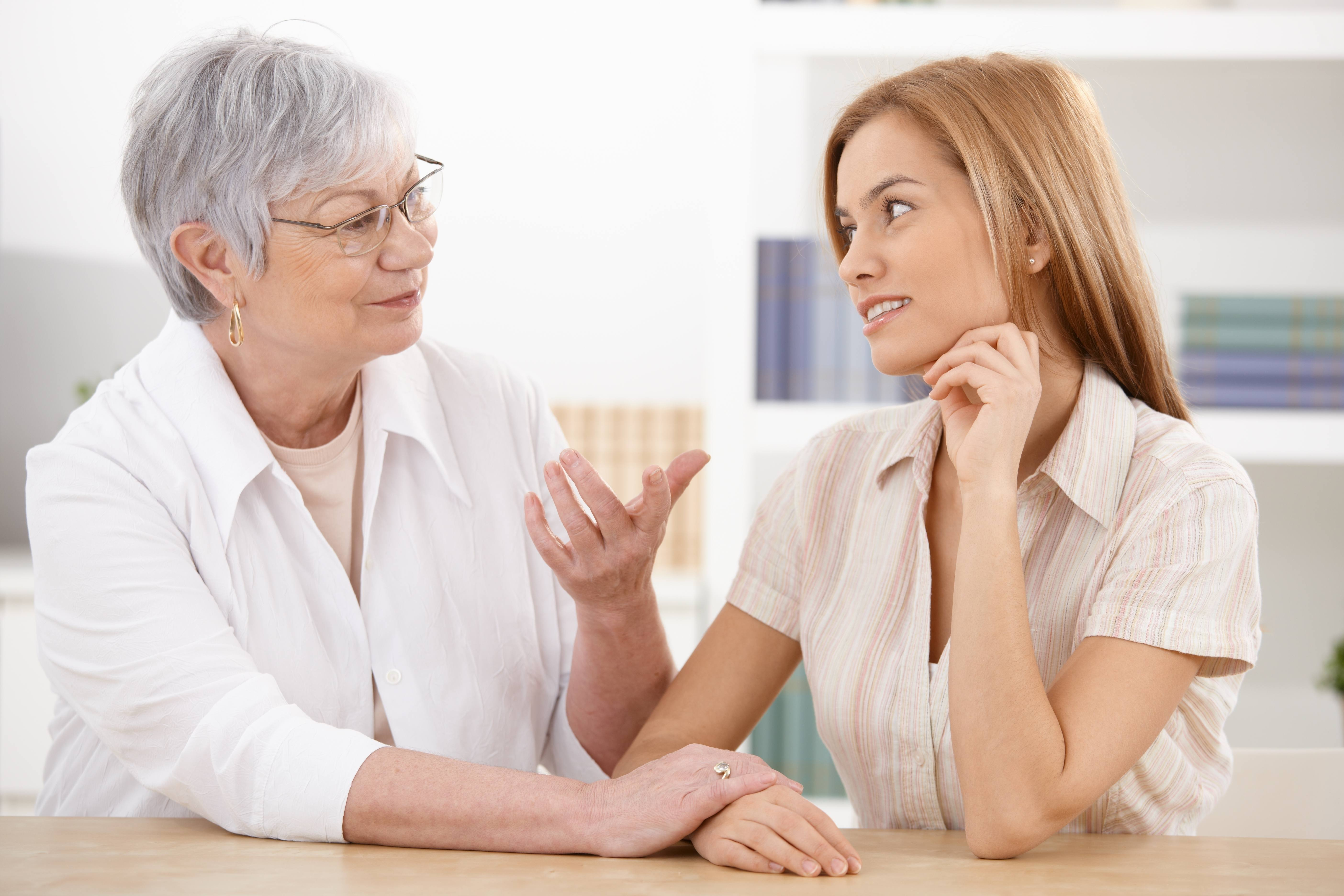 older woman talking with younger woman at table