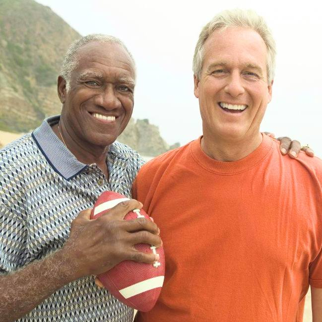 two smiling men standing together on a beach, one holding a football in one hand with the other arm around his friend's shoulders