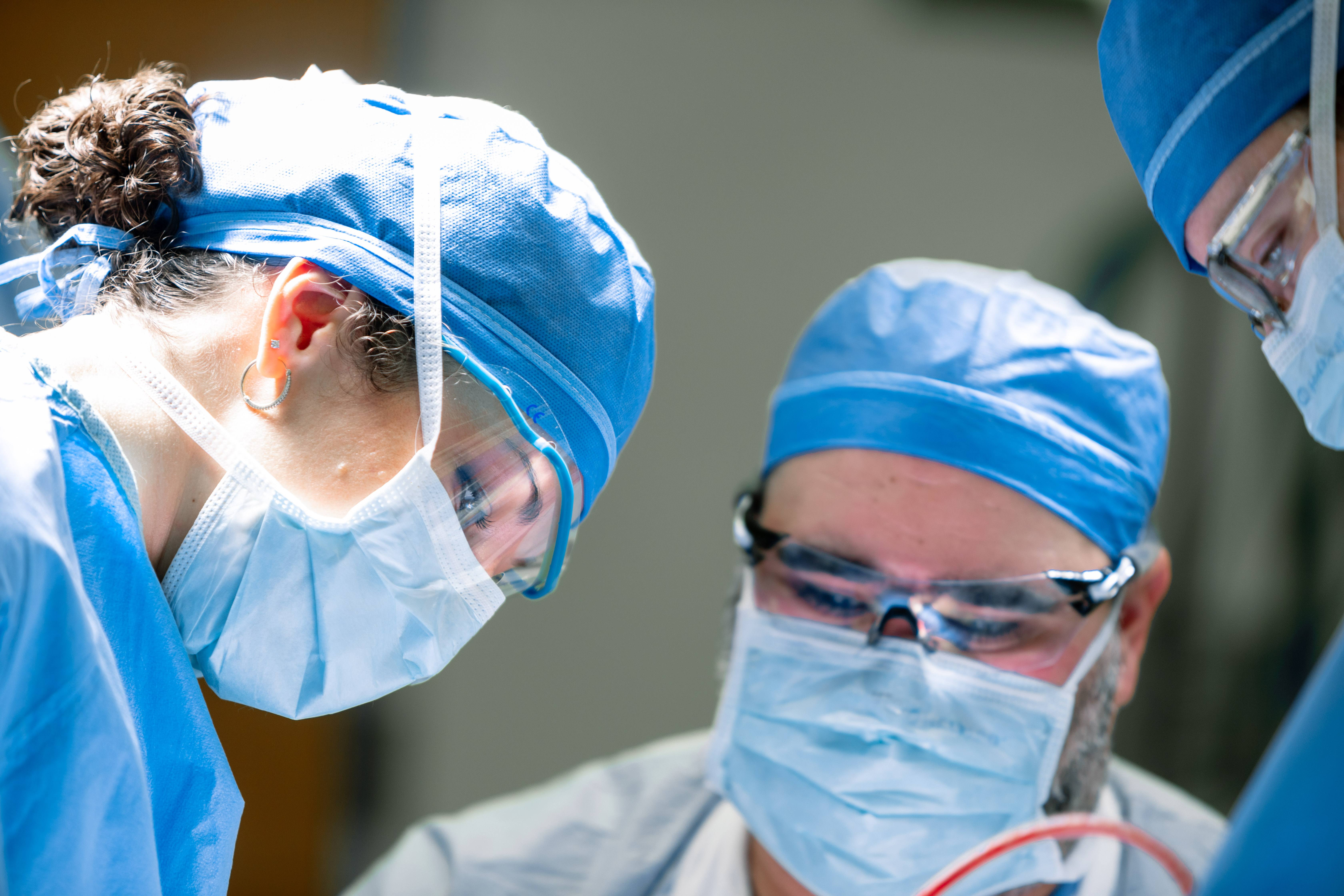 three surgeons operating on a patient while bending over