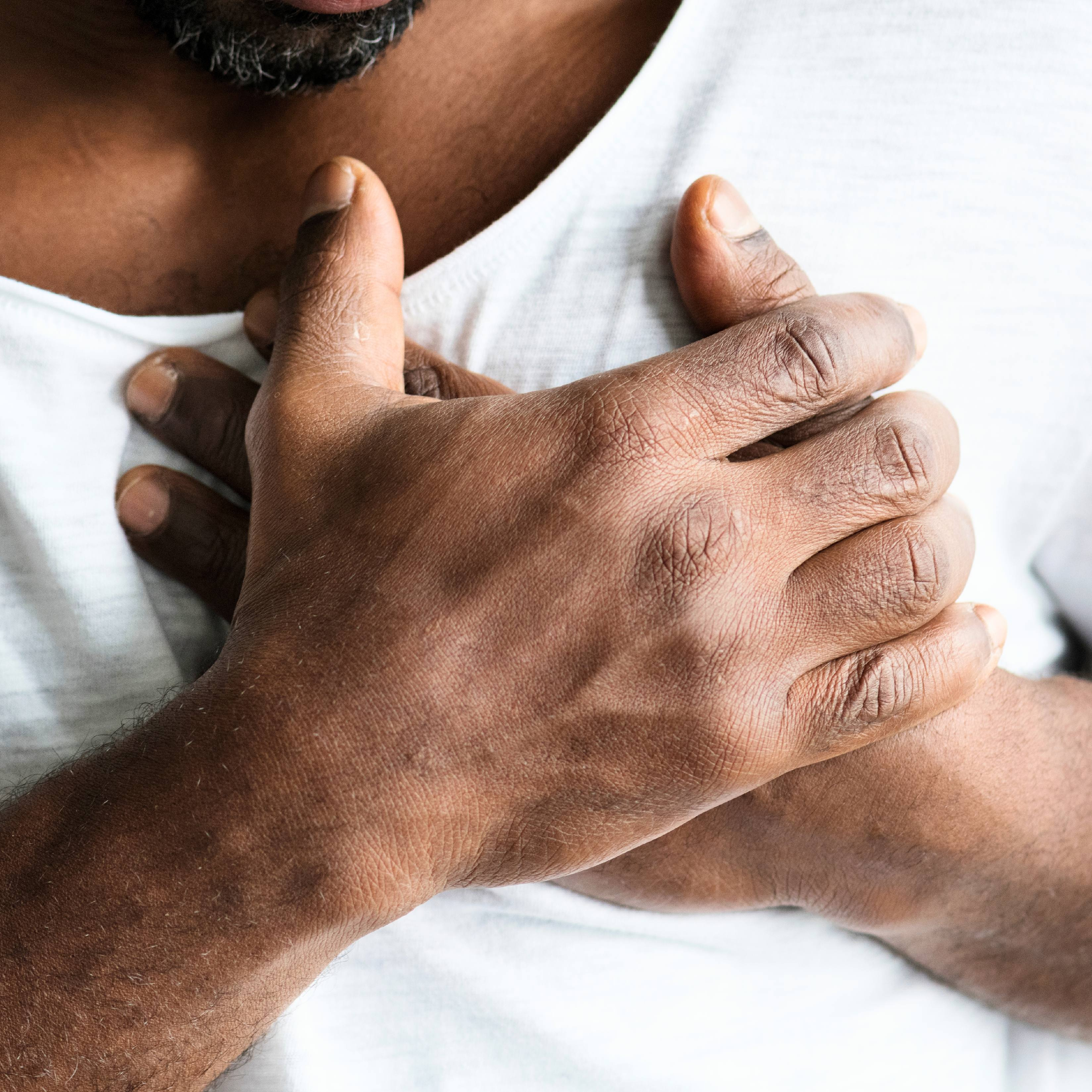 a closeup of a Black man in a t-shirt grasping his chest as if he's having heart pain or a heart attack