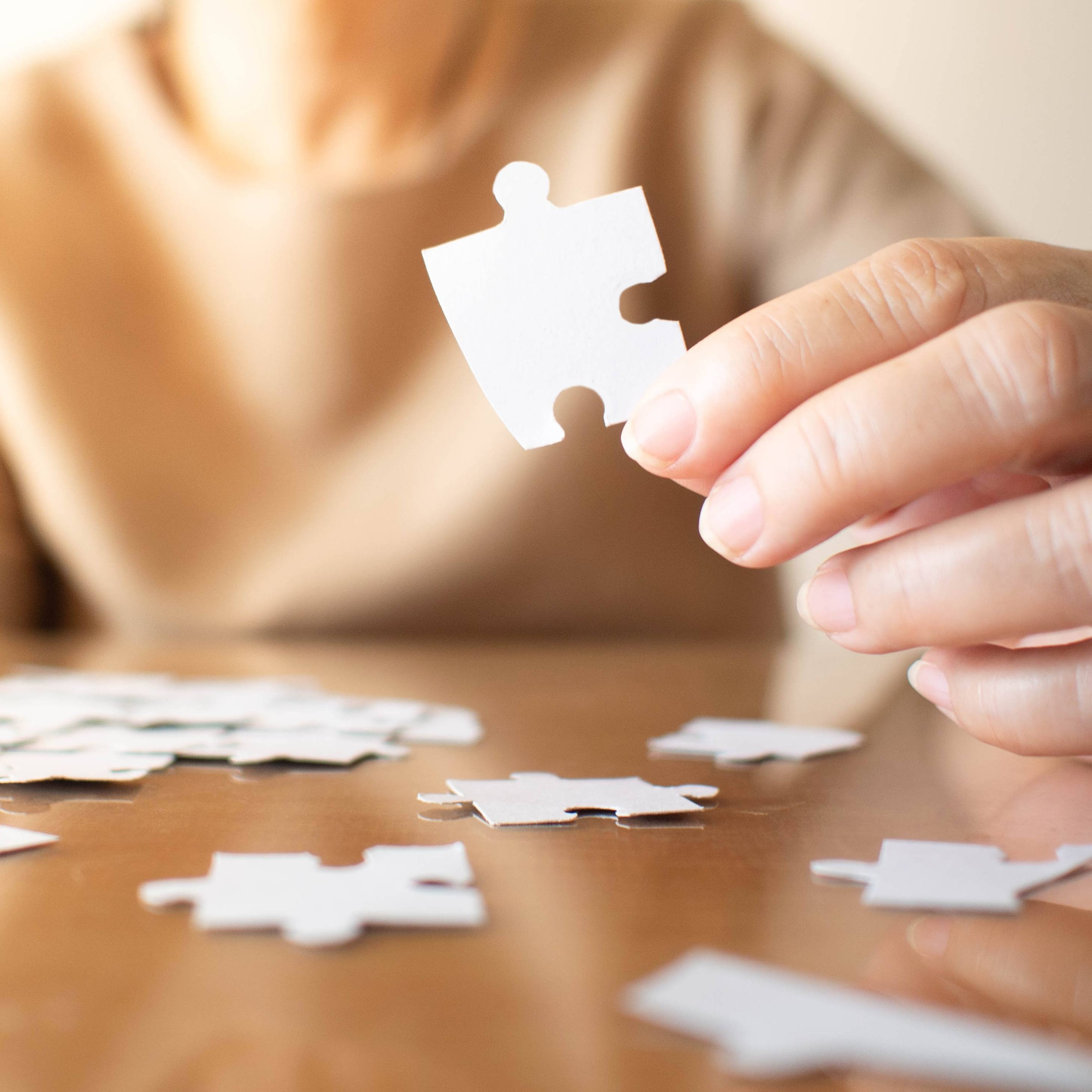 Elderly female hand trying to connect pieces of white jigsaw puzzle on wooden table.