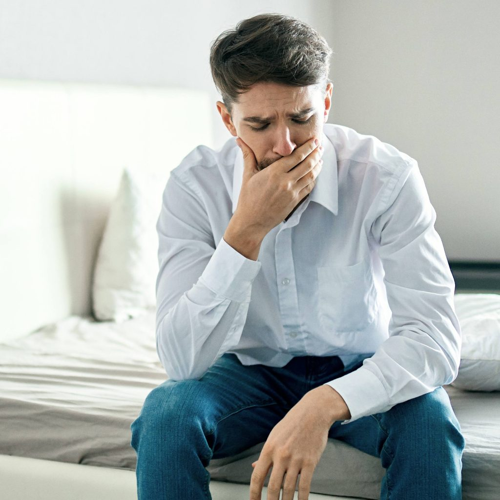 a young white man sitting on the edge of a bed, with his hand on his face looking sad, concerned, worried, stressed and depressed