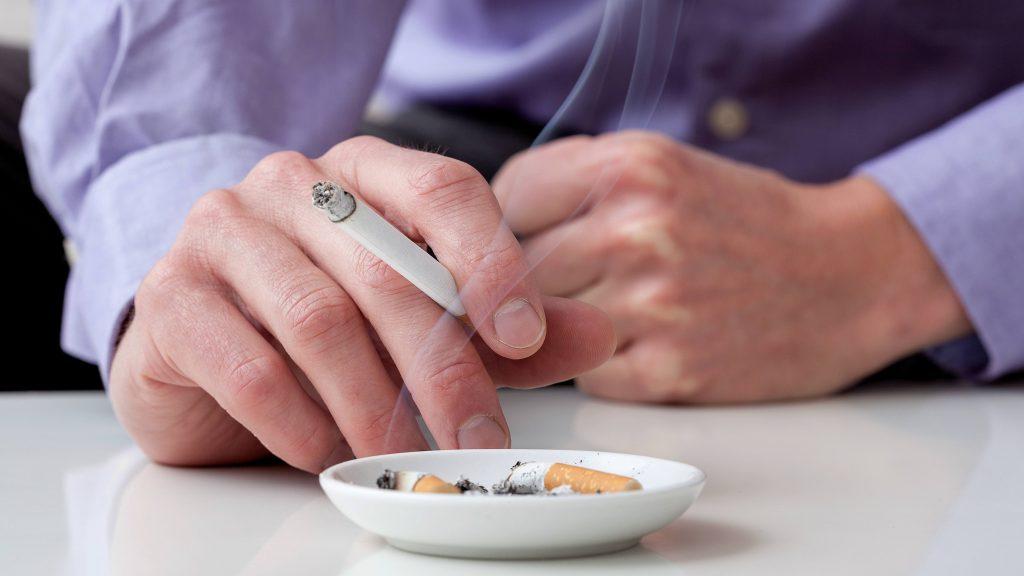 Un hombre con camisa azul fuma un cigarrillo