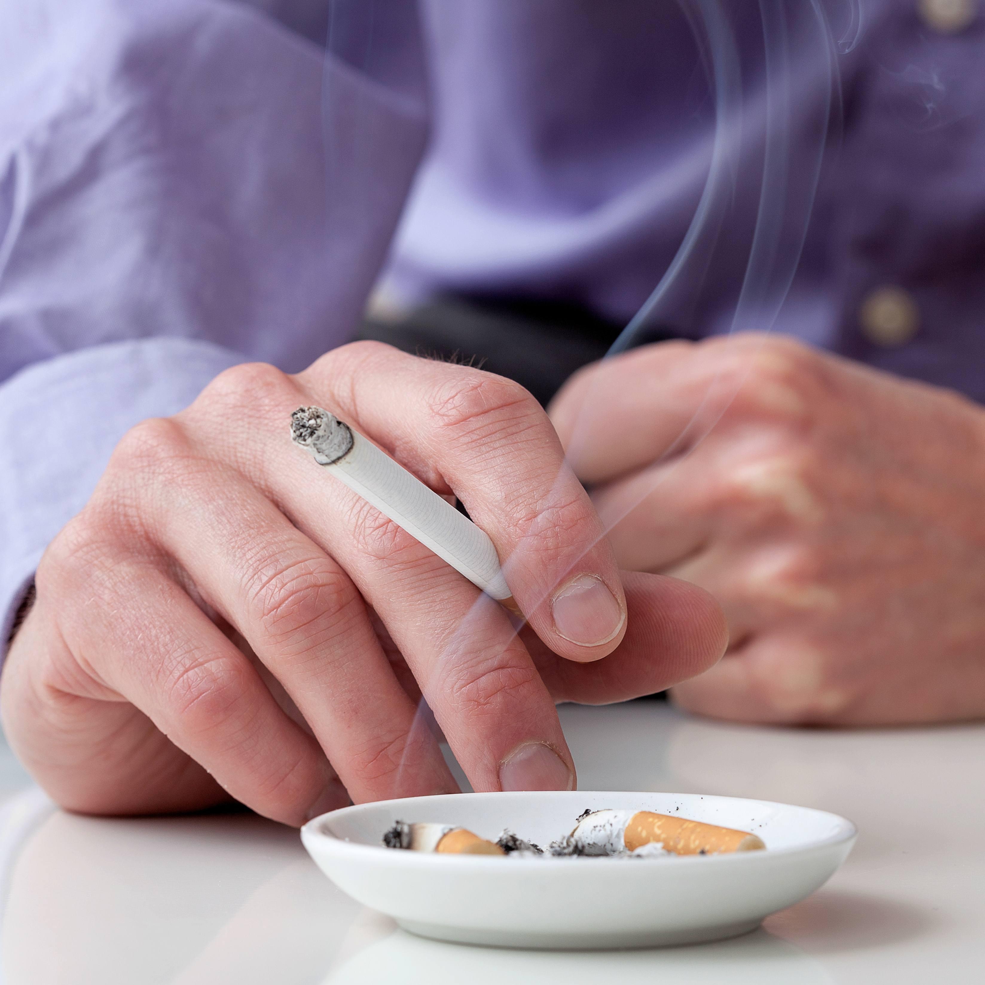 Man in blue shirt is smoking cigarette