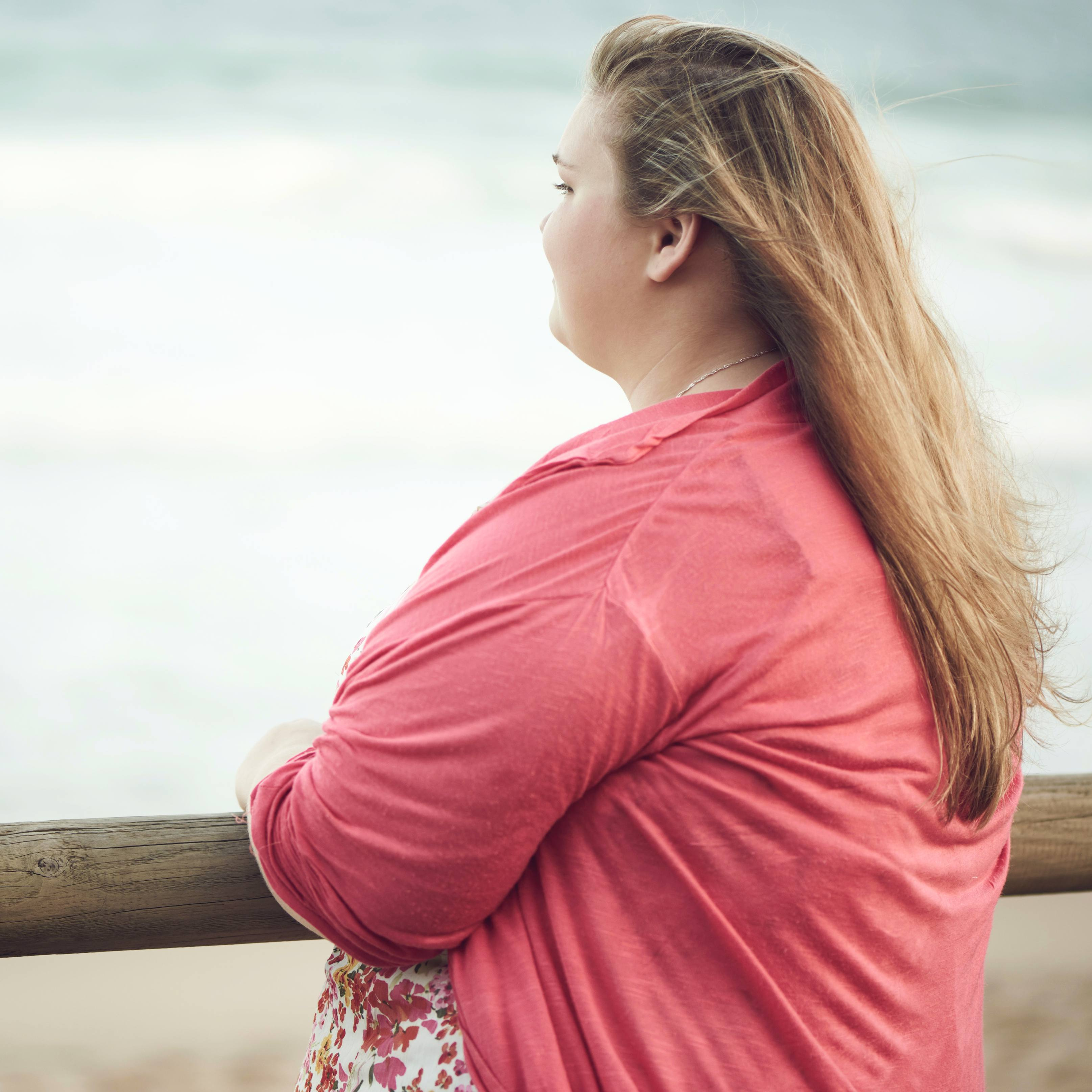 young overweight obese woman looking out at the ocean