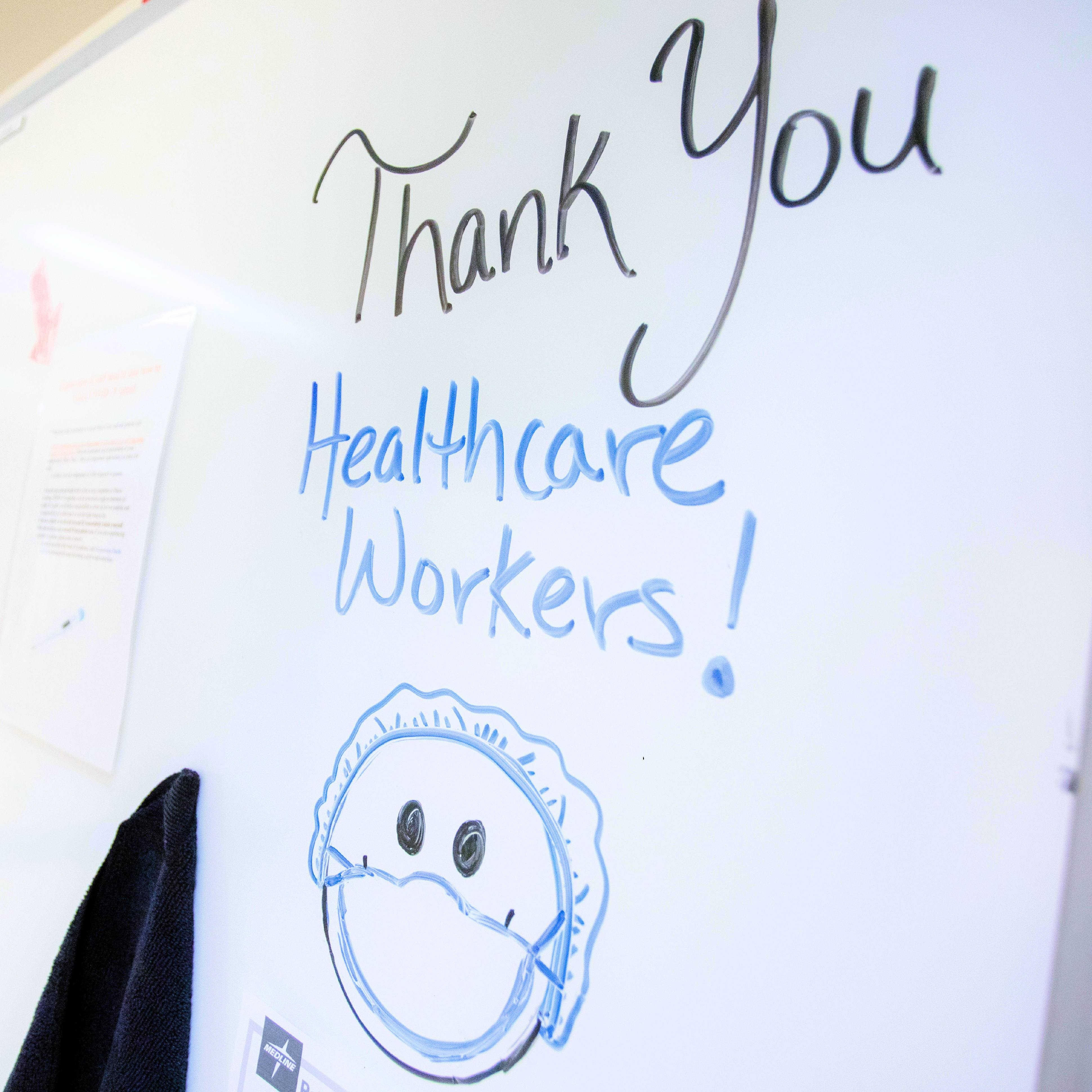 a 'Thank You Healthcare Workers' sign on a wipe board in a hospital hallway