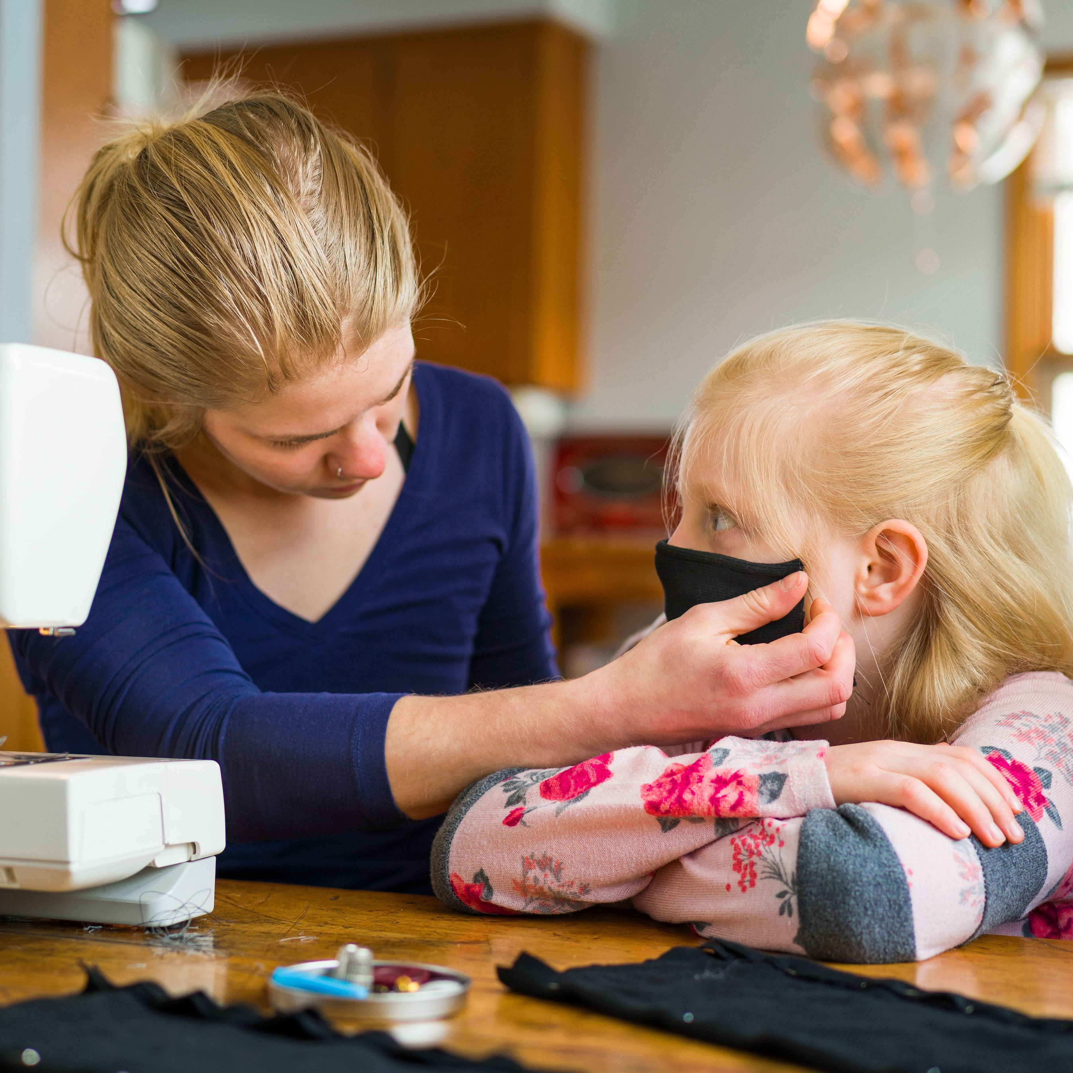 a young Caucasian woman at a sewing machine making face masks and with a little Caucasian girl sitting next to her and trying on one of the masks