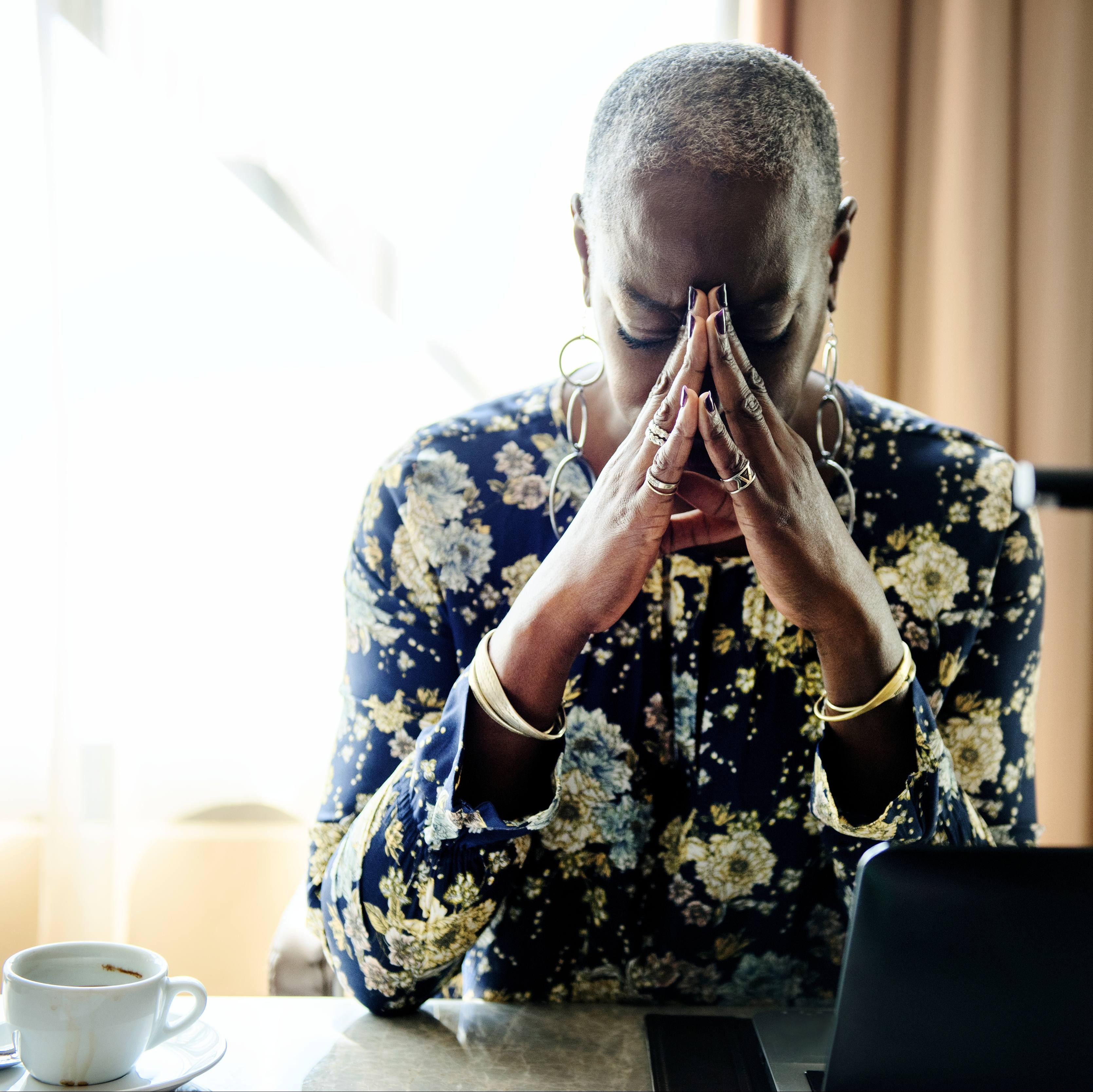 an African American woman sitting at a desk near a window with the light coming in and resting her head on her hands in a prayer-like position, perhaps worried or stressed