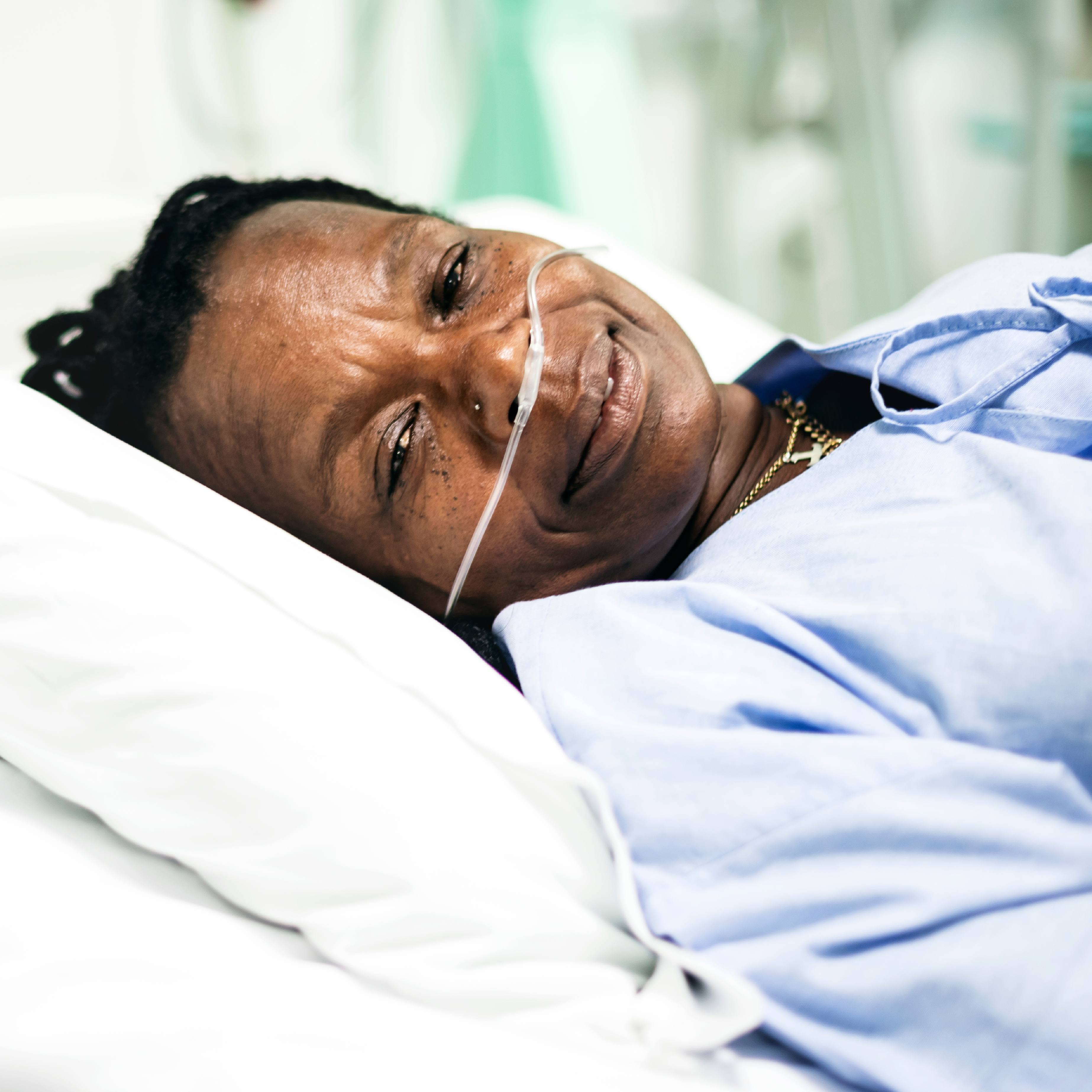 an African American woman slightly smiling in a hospital gown, resting on a pillow with oxygen tubes in her nose