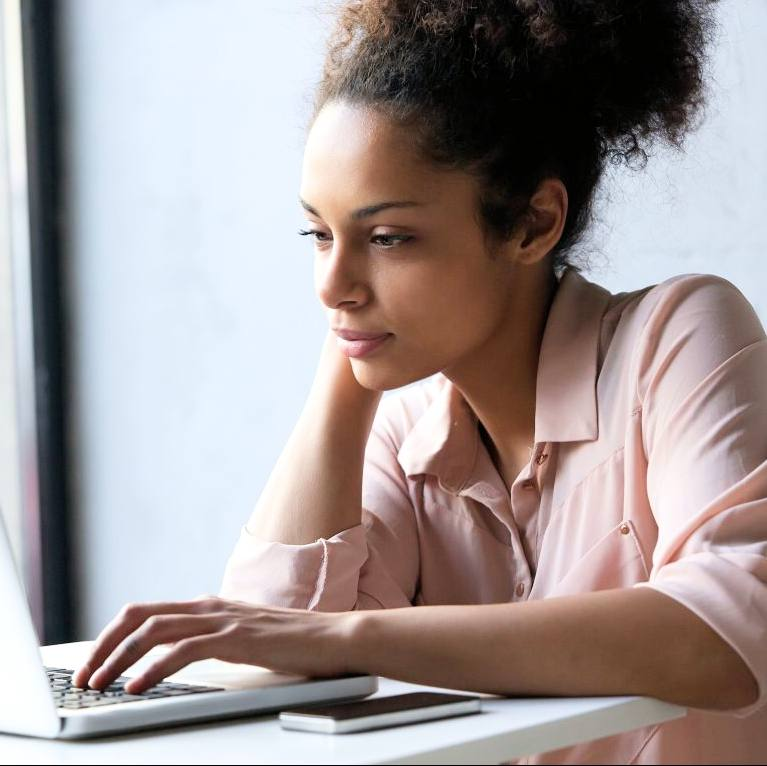 a young African American or Latina woman reading information on a laptop computer, looking thoughtful, serious