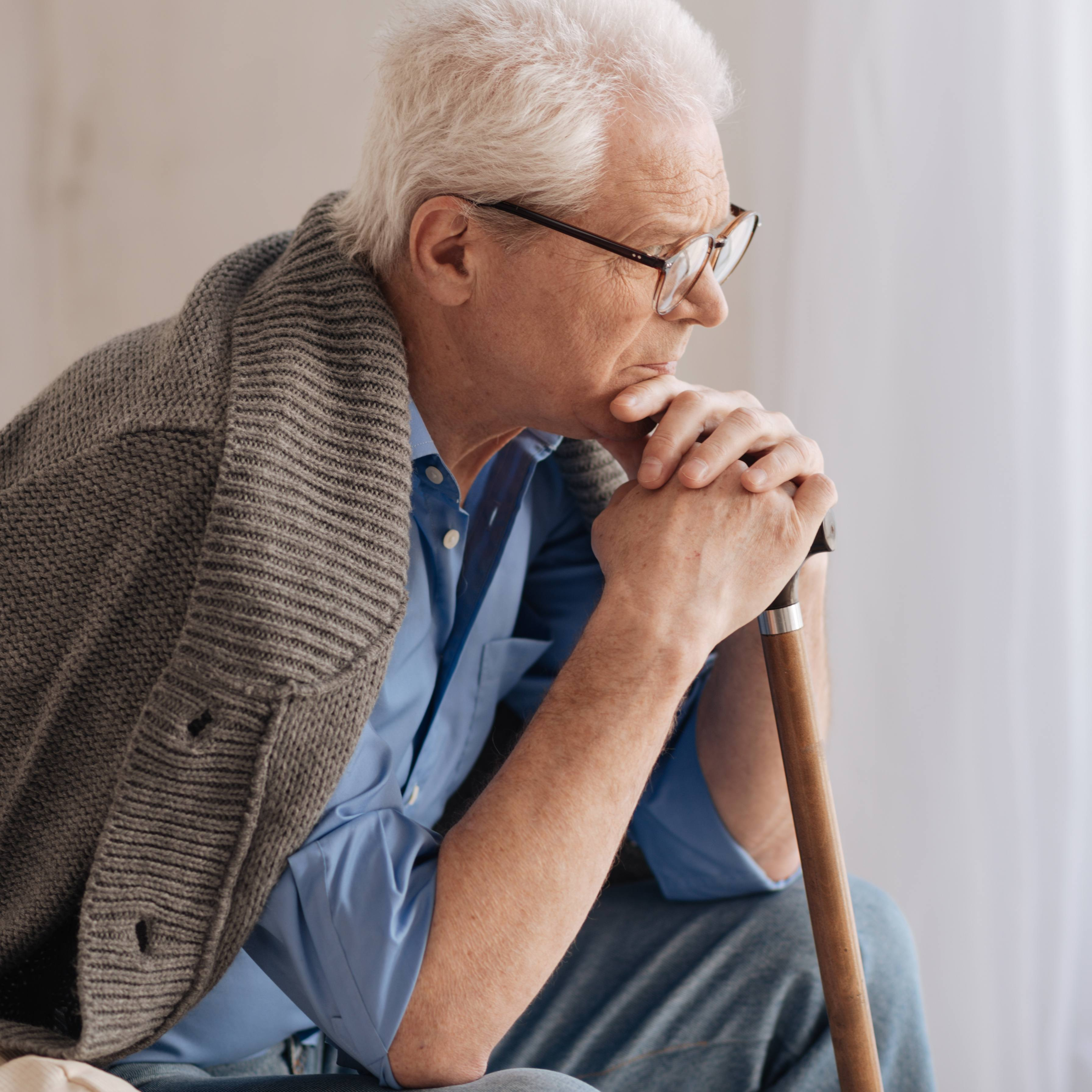 an older Caucasian man with glasses, leaning on a cane while sitting in a chair near a window and looking concerned, worried, thoughtful