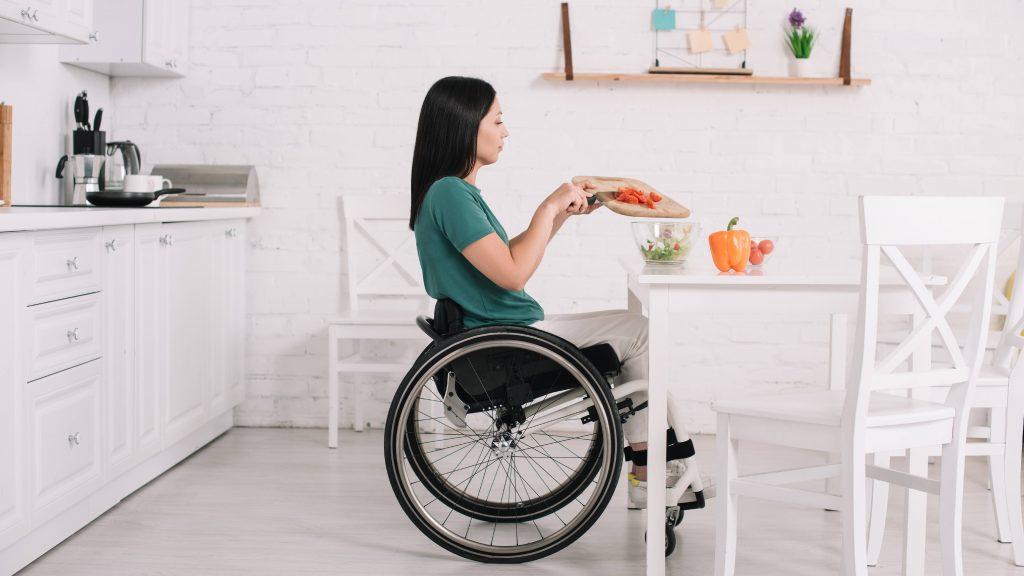 Vista lateral de una mujer discapacitada que está sentada en una silla de ruedas y cerca de una mesa preparando una ensalada