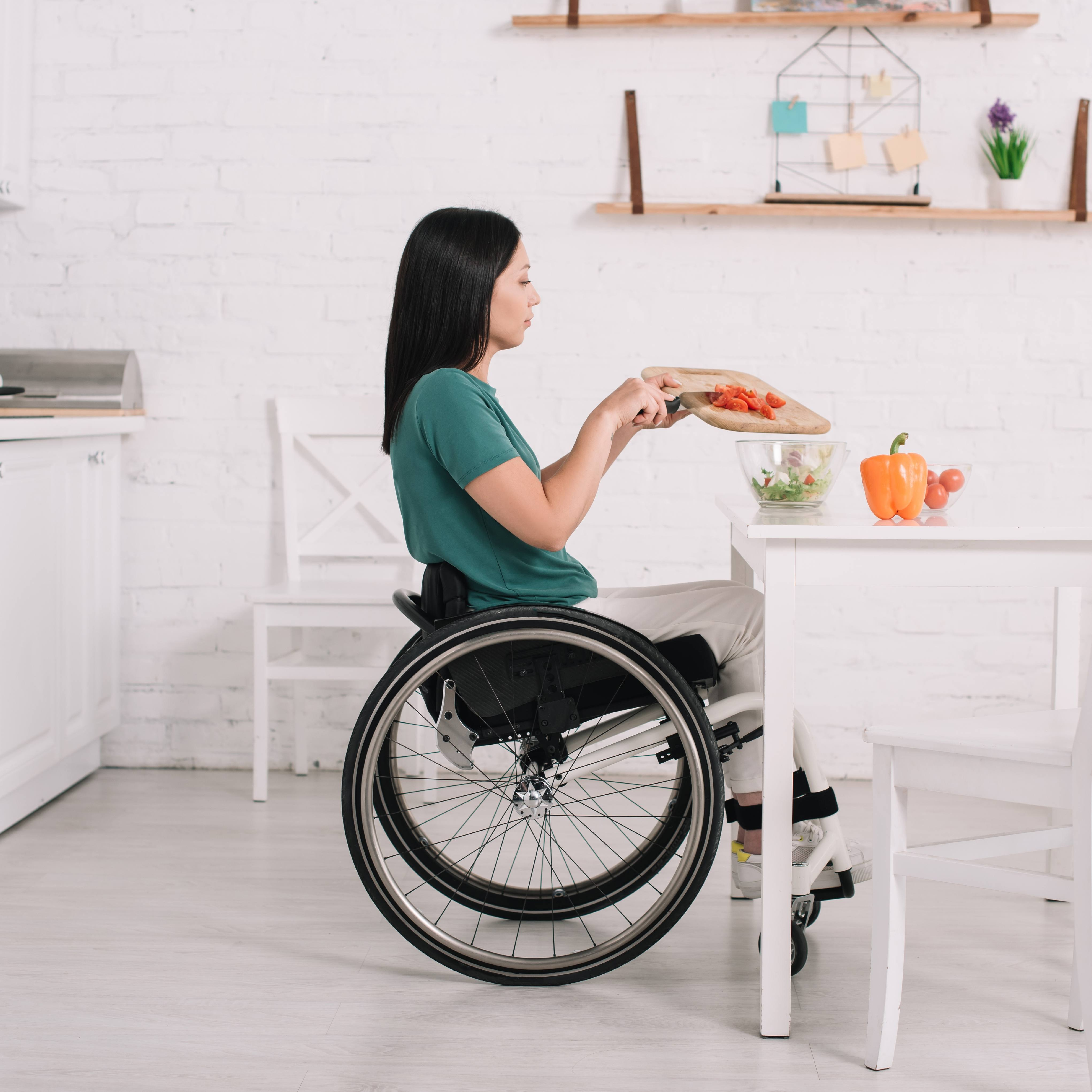 side view of disabled Caucasian or Latino young woman preparing salad while sitting on wheelchair near table