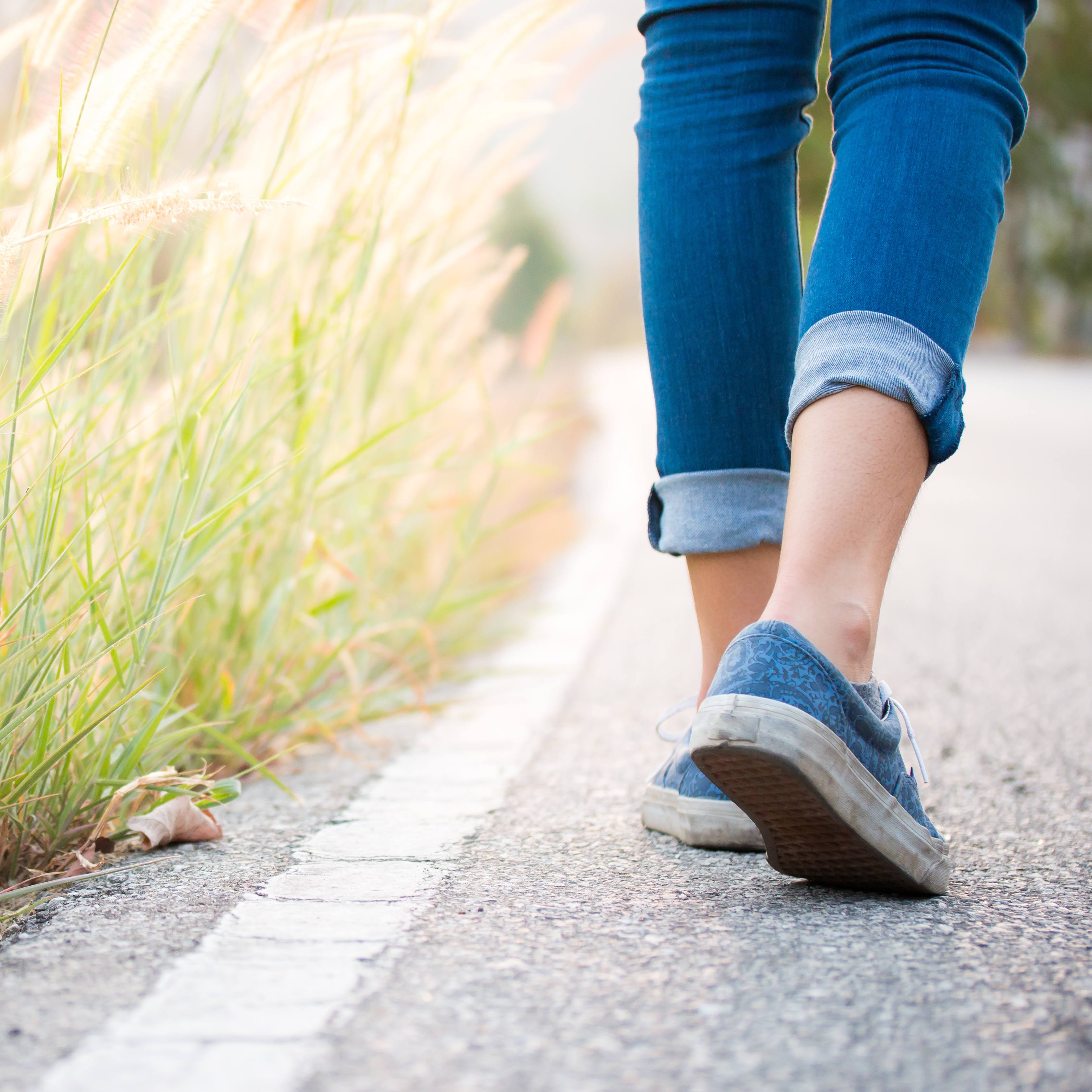 a closeup from behind of a Caucasian woman's leg and feet, wearing jeans and tennis shoes walking down a paved road beside tall grass