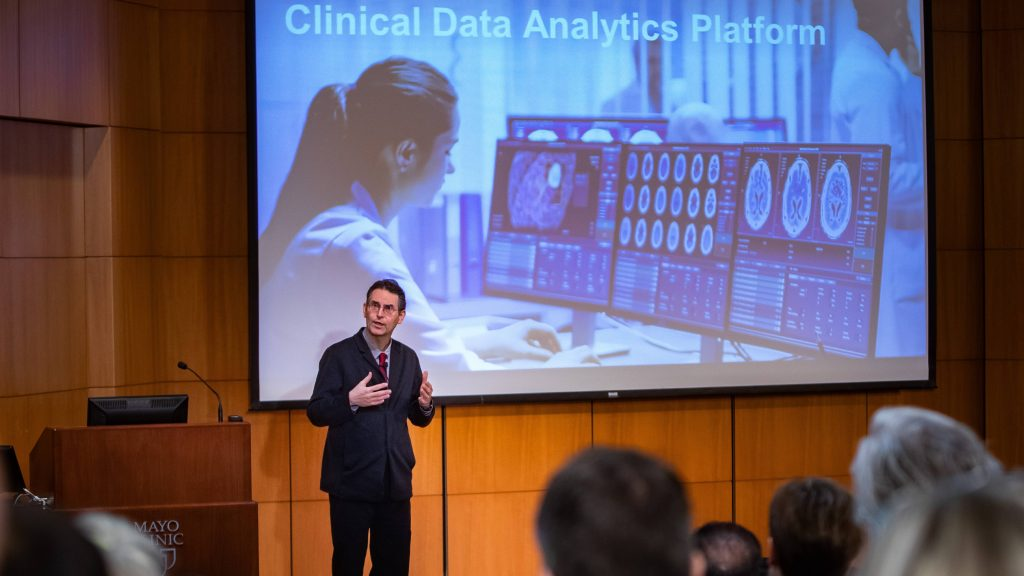 Dr. John Halamka giving a Mayo Clinic presentation with a screen behind him