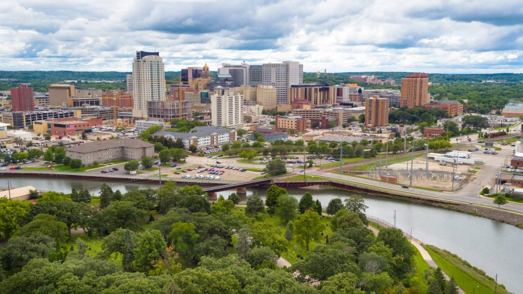 a landscape photo of downtown Rochester Minnesota, including the Mayo Clinic campus with a blue sky, some clouds and the Zumbro River with green trees in the foreground