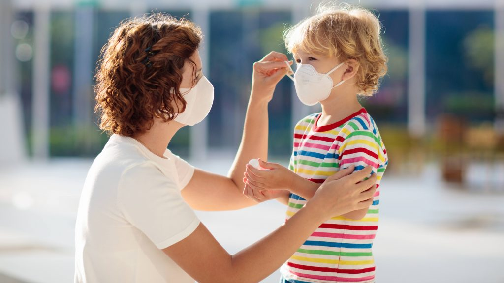 a white adult woman, perhaps a mother, wearing a mask and adjust the face mask on a young child