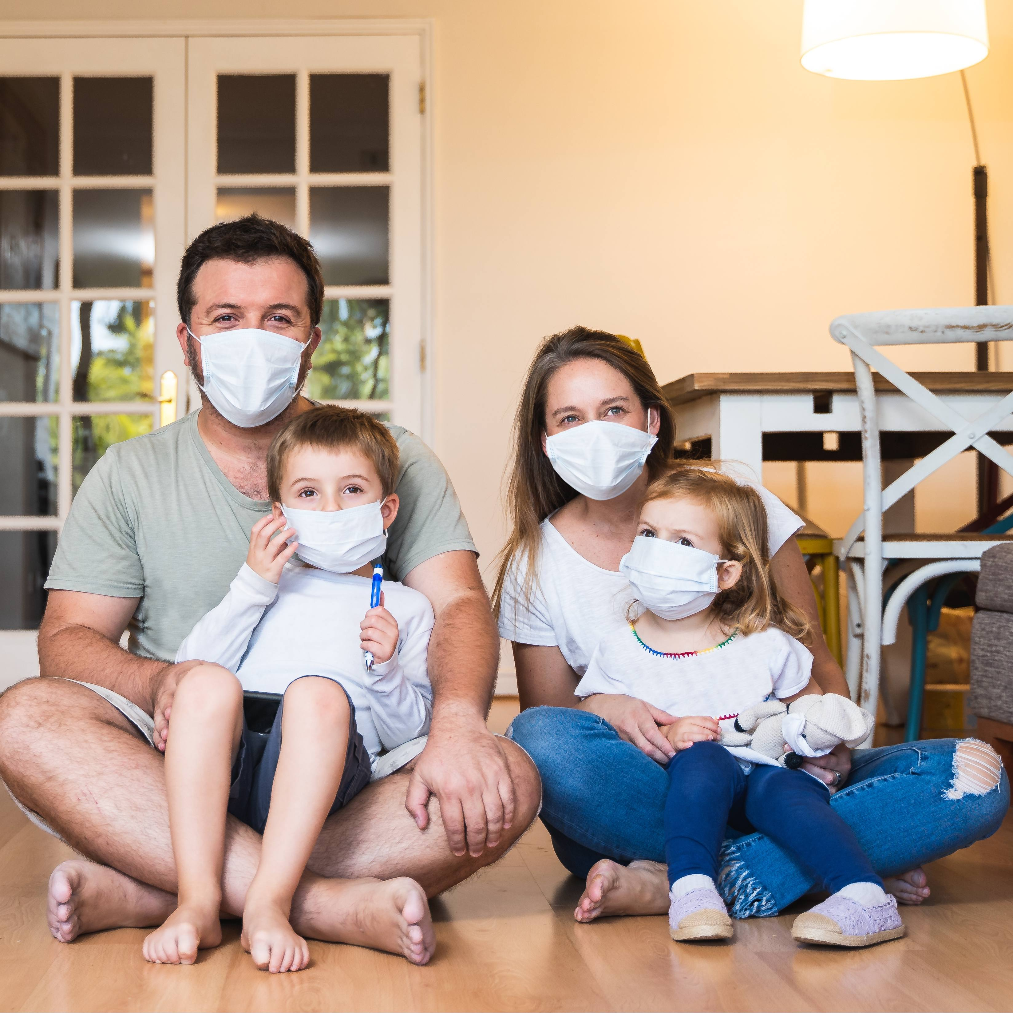 a white man and woman with two white children sitting on their laps on the floor, smiling and wearing face masks