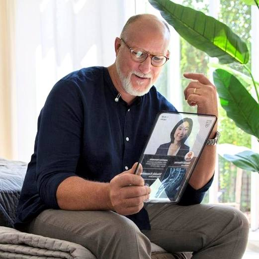 a white man with glasses and a beard, sitting on a bed near a window and house plant, holding an Ipad or computer tablet