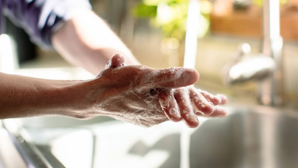 a white person washing his of her hands with soap in a stainless steel kitchen sink near a window with sunlight