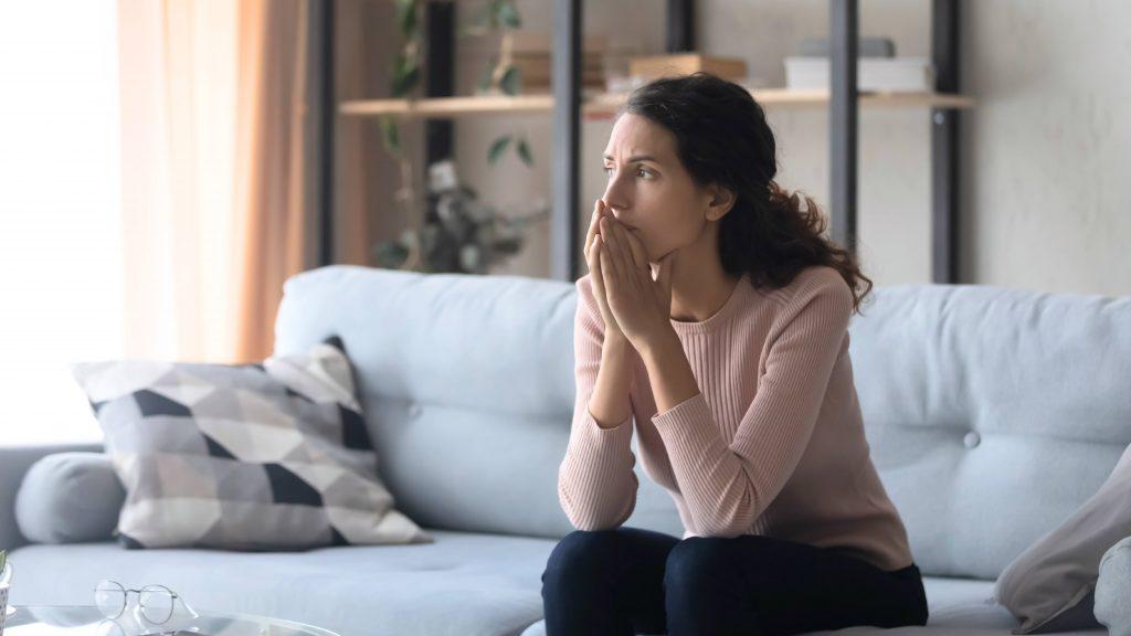 Mujer sentada en un sofá mirando por la ventana, cruzando las manos y luciendo triste, preocupada, preocupada