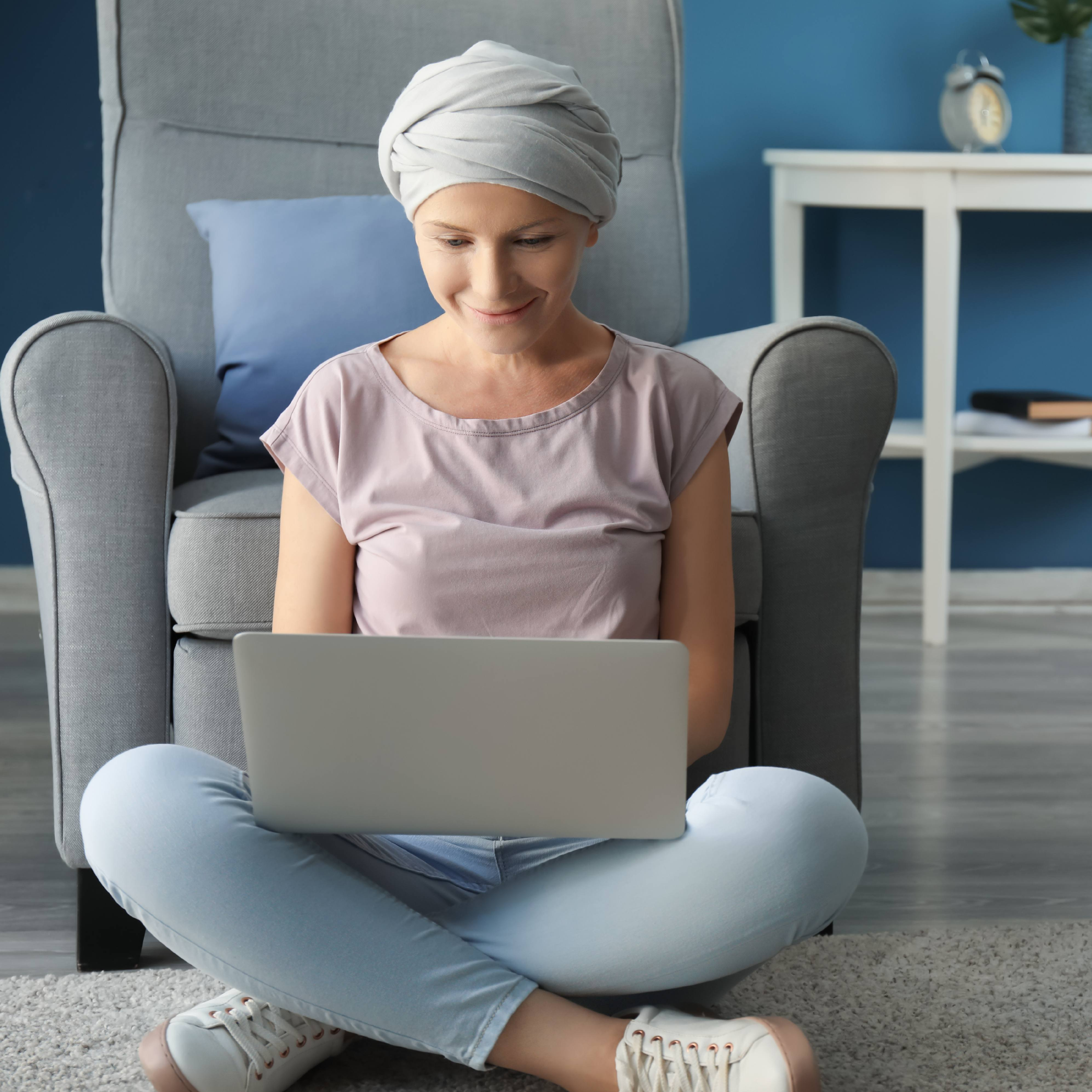 a young white woman wearing a head scarf and sitting on the floor in her home, smiling and working on a computer laptop