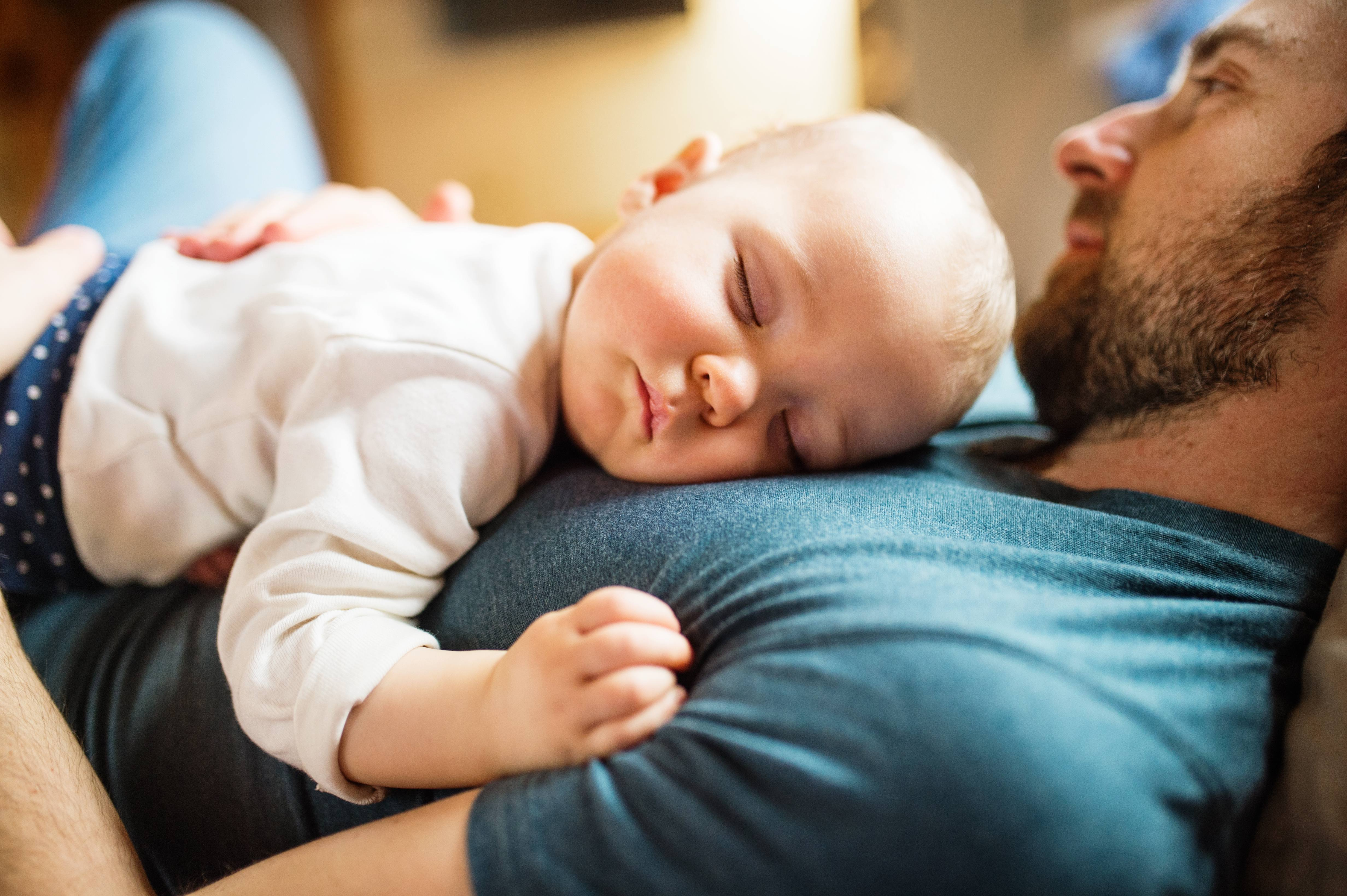 a white man in a blue t-shirt resing on his back with an white infant, baby sleeping on the man's chest