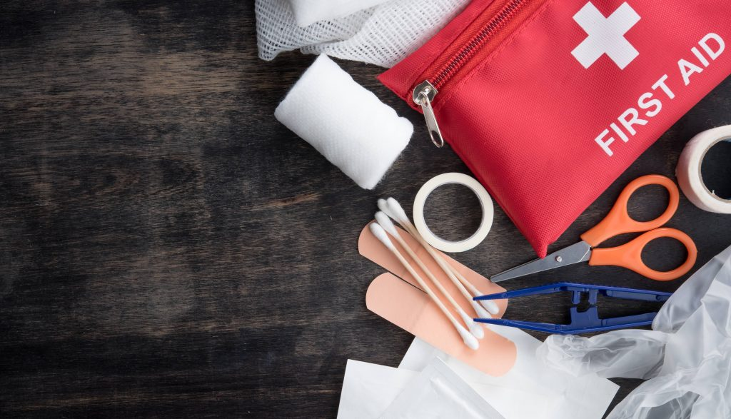 a red and white First Aid kit on a table with bandages, medical tape, tweezers and scissors