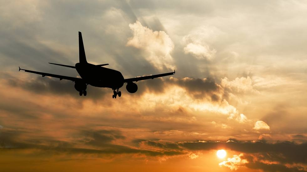 silhouette of a commercial airplane flying through clouds and toward the sun