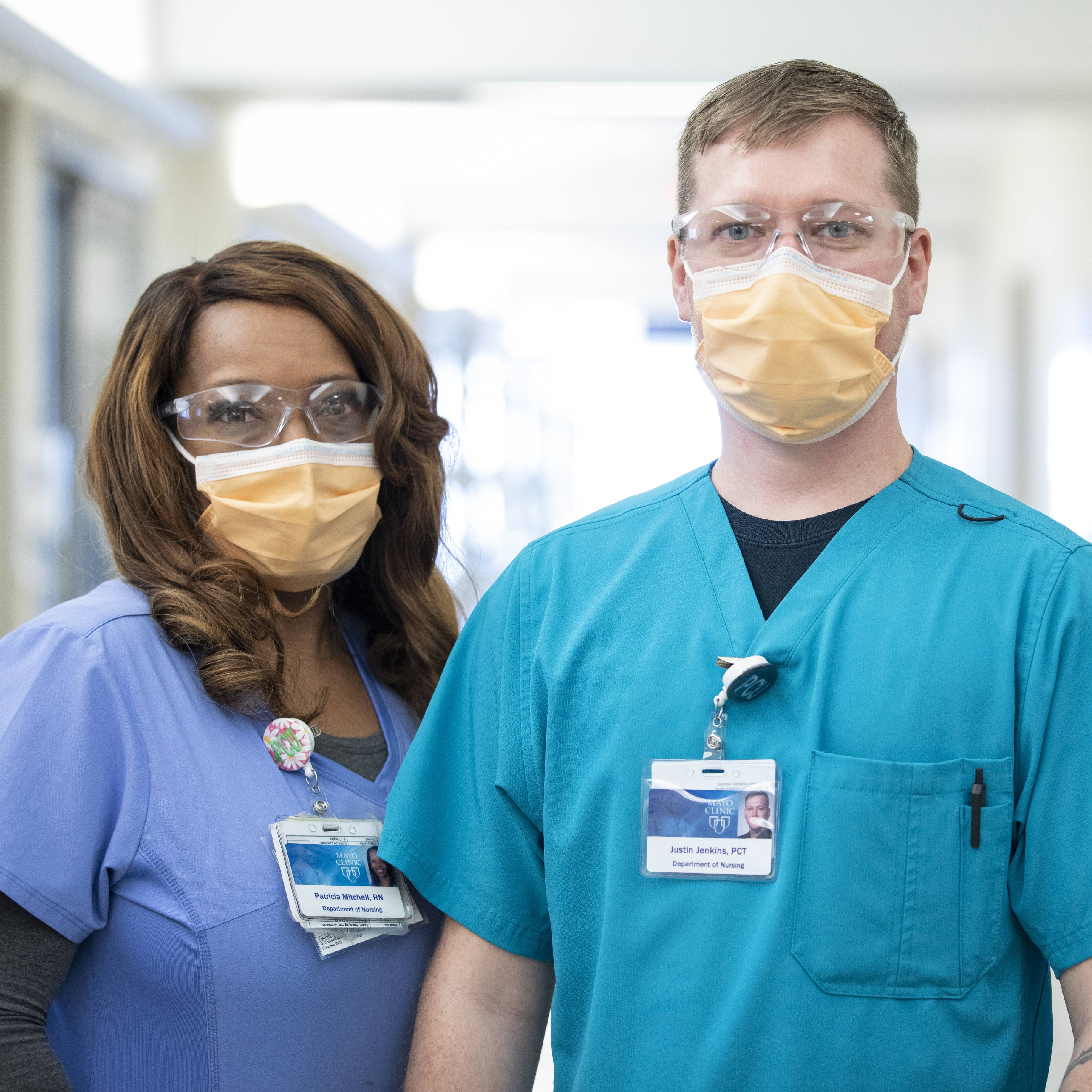 two Mayo Clinic employees in medical scrubs wearing face masks and eye coverings