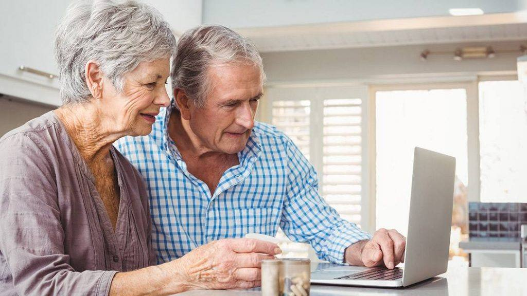 an older white couple with gray hair sitting at a table and looking at a laptop computer and smiling