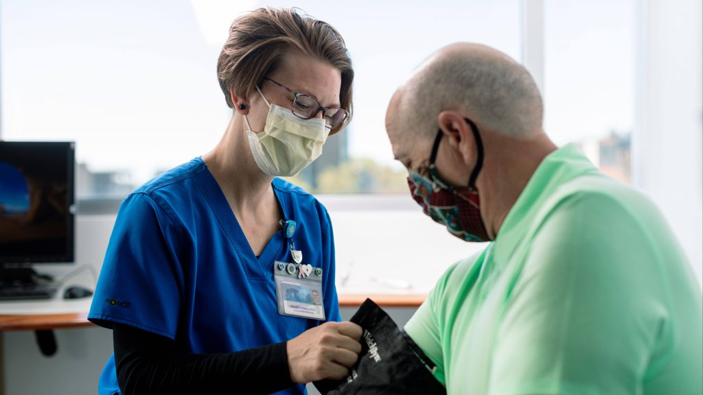 a white woman, Mayo Clinic health care worker in blue scrubs and wearing a mask is taking a white man's blood pressure, who is also wearing a mask