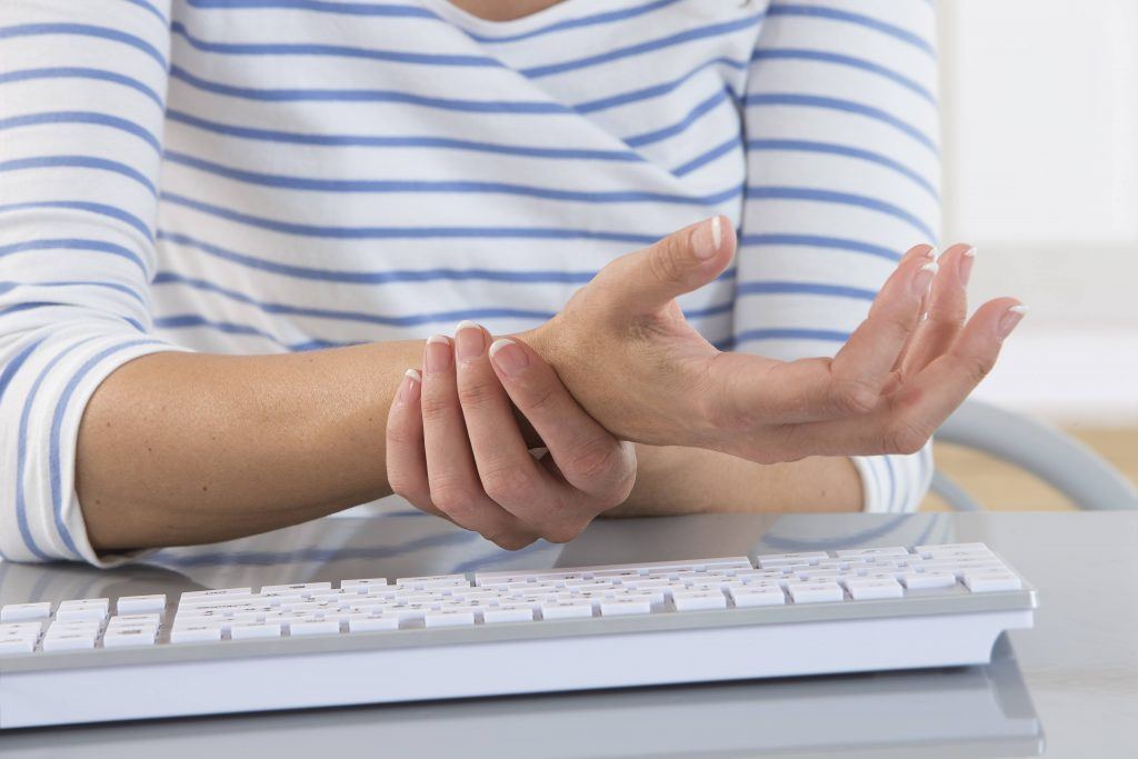 a white woman in a striped shirt near a computer keyboard holding her wrist because it's injured, sore, in pain