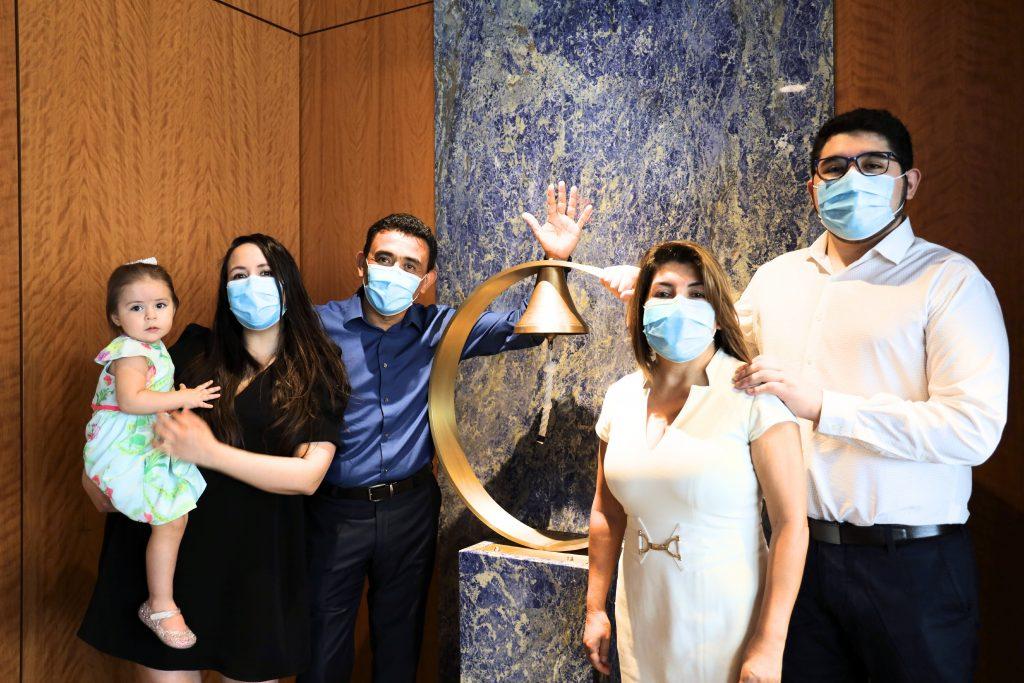Eduardo Agüero, paciente de cáncer de Mayo Clinic Florida, con su familia después del último tratamiento de quimioterapia, todos con mascarillas protectoras, mientras toca el timbre porque su tratamiento ha terminado